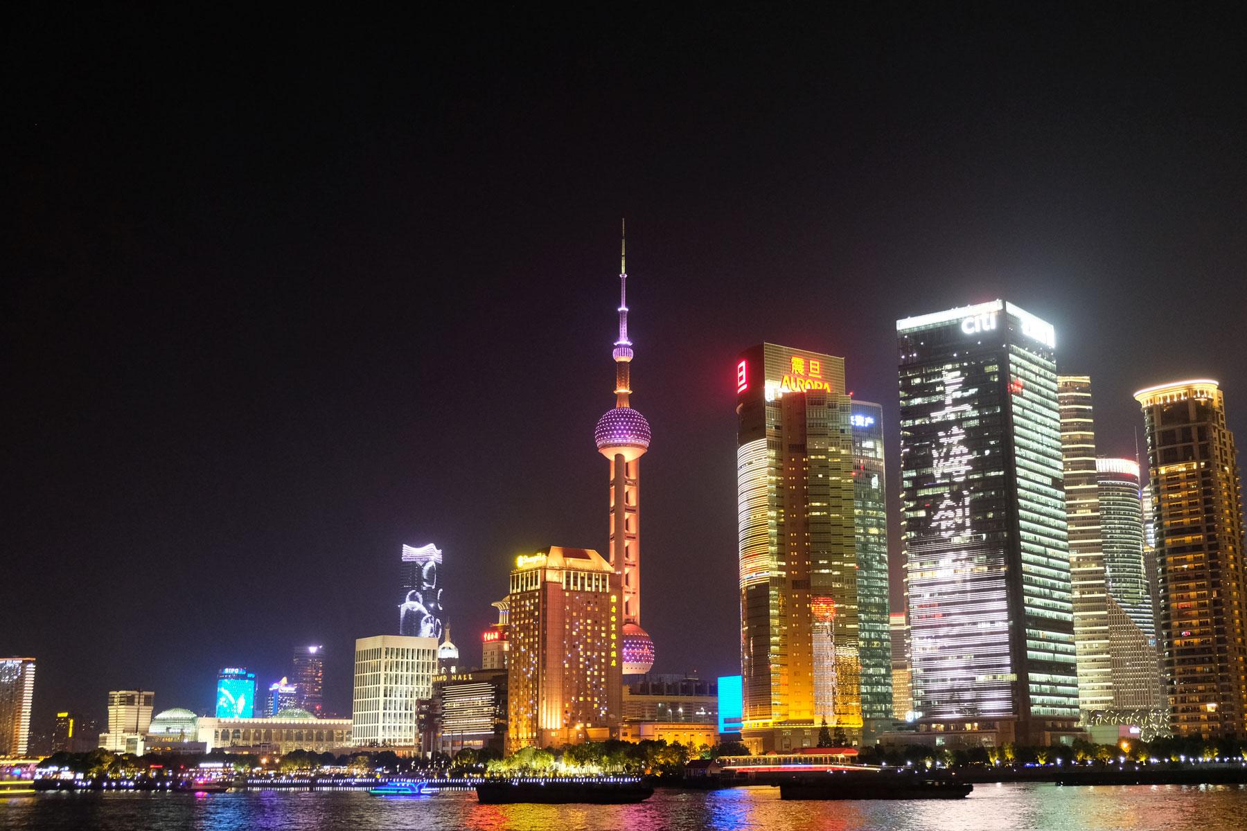Am Huangpu-Fluss leuchtet Shanghais Finanzzentrum in der Nacht.
