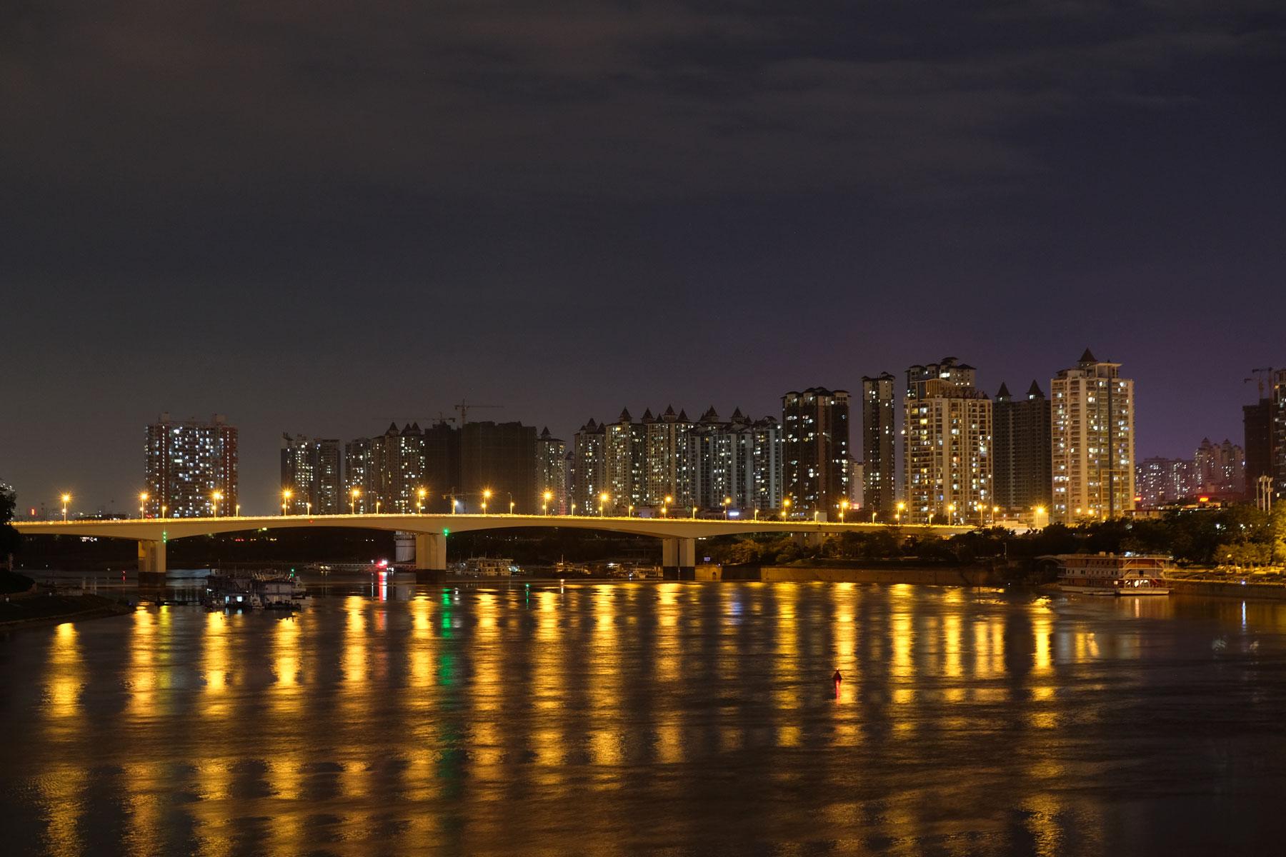 Beleuchtete Hochhäuser leuchten über den Fluss hinweg in Nanning in China.