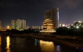 Am Fluss in Nanning leuchtet ein Tempel in der Nacht, neben ihm die Hochhäuser.