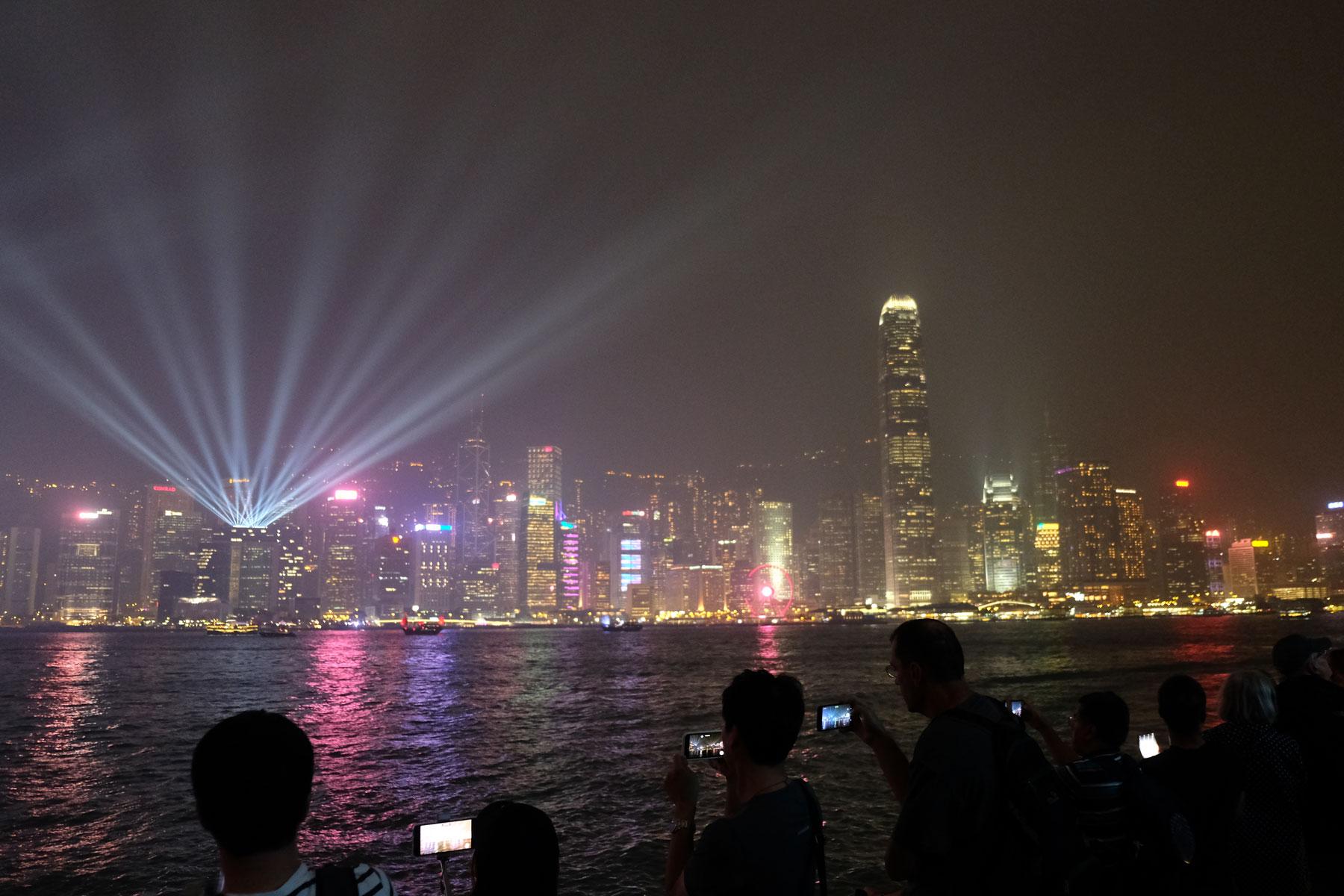 Menschen fotografieren mit ihren Handys die Lightshow auf der Hongkong Island.