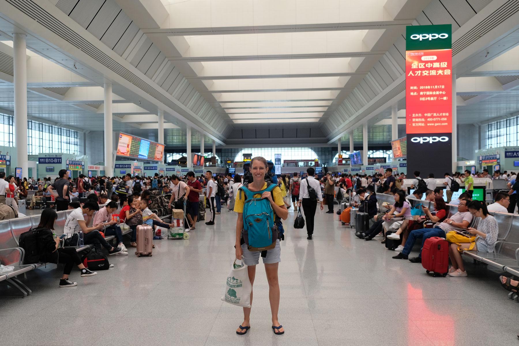 Leo steht mit ihrem Gepäck in der Halle des Bahnhofs Nanning in China.