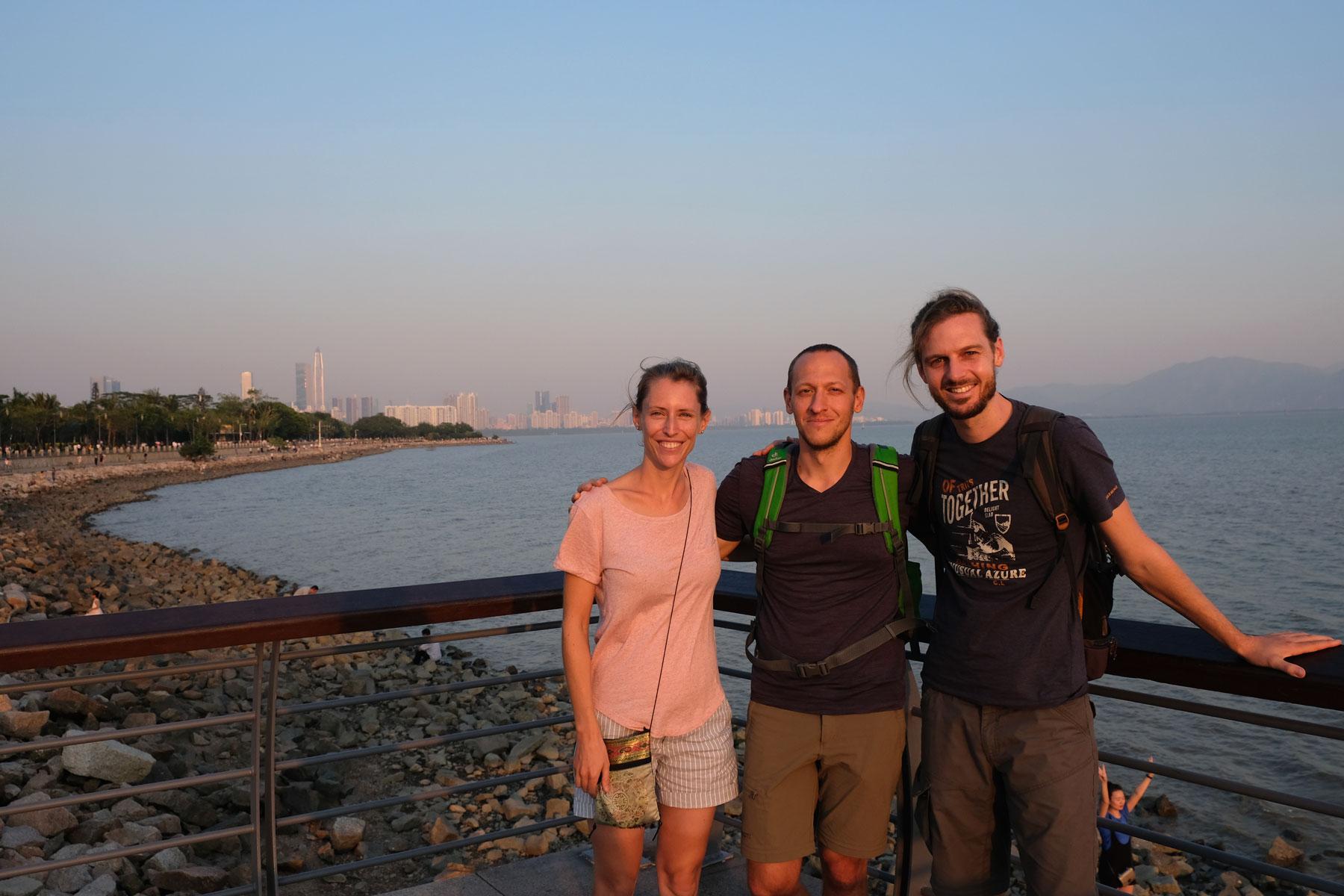 Leo und Sebastian stehen mit ihrem Freund Curtis an der Bucht von Shenzhen.