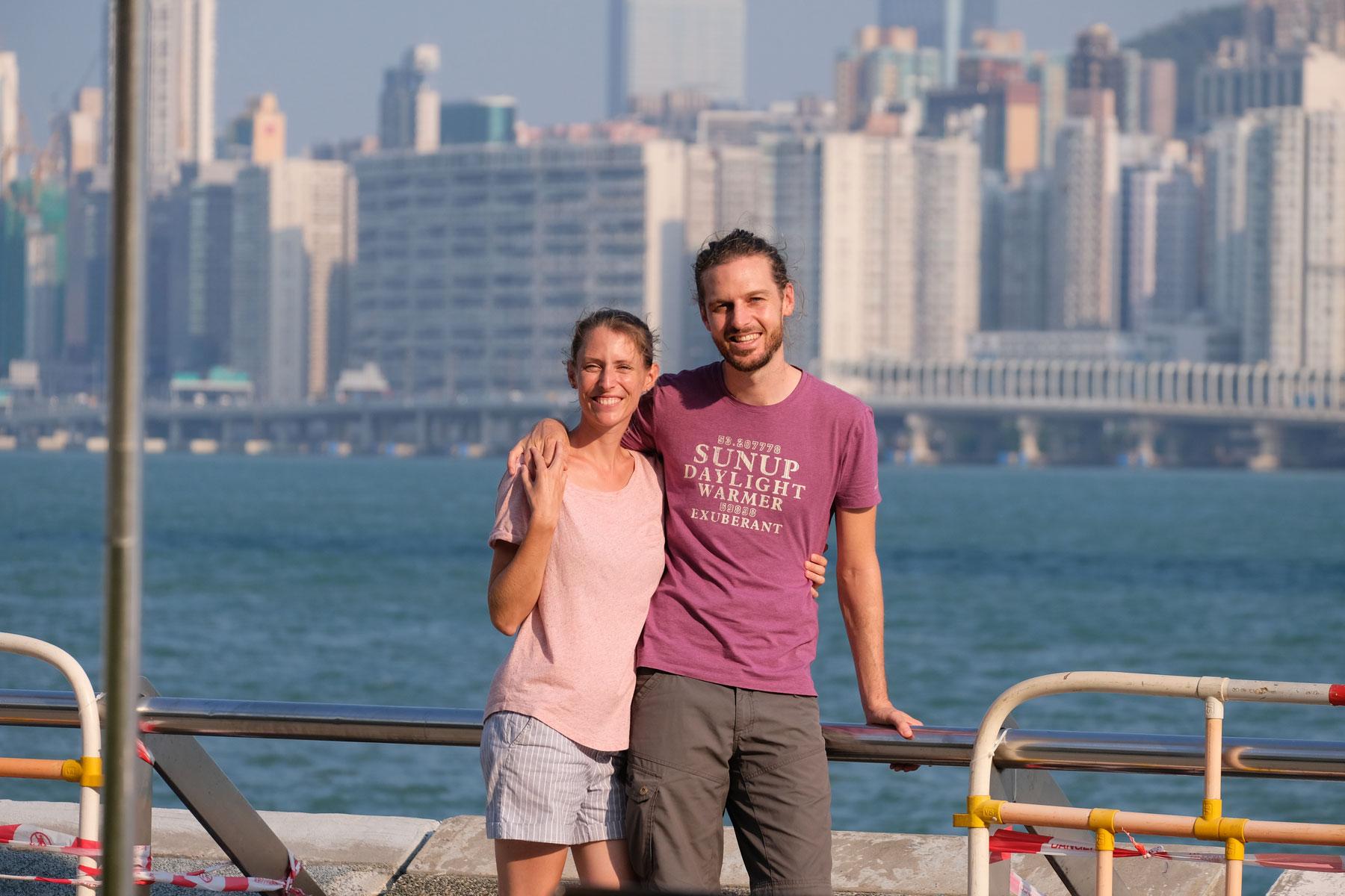 Leo und Sebastian von eins2frei stehen an der Promenade vor der Skyline der Hongkong Island.