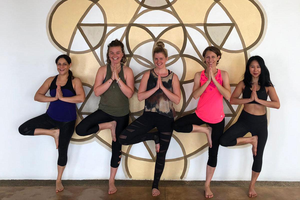 """Leo steht mit ihren Mitteilnehmerinnen in der Yogaposition """"Der Baum"""" vor einem Mandala in Sayulita in Mexiko."""
