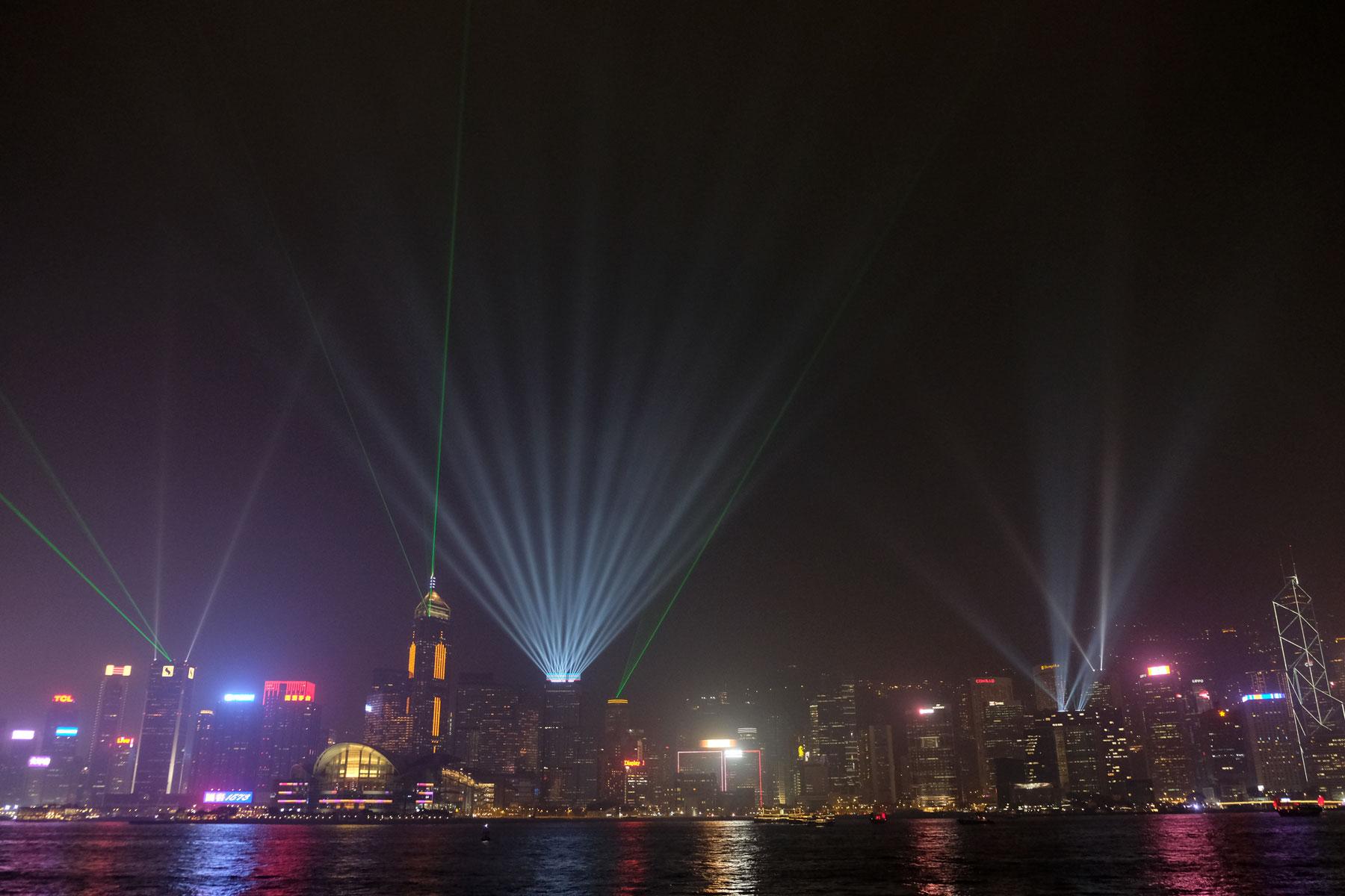 Für die Lightshow in Hongkong leuchten riesige Scheinwerfer von den Hochhäusern.