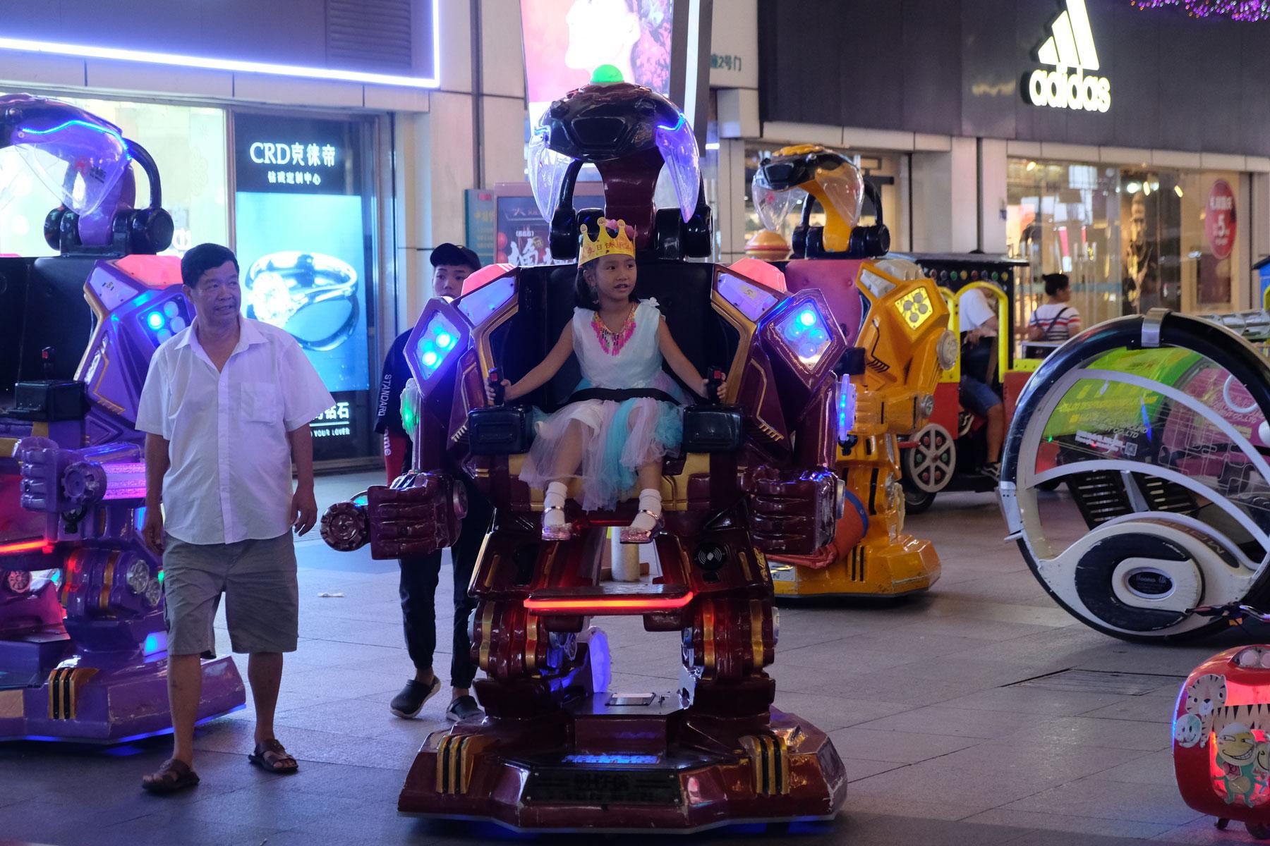 Ein Mädchen fährt auf einem Roboter in Nanning in China.