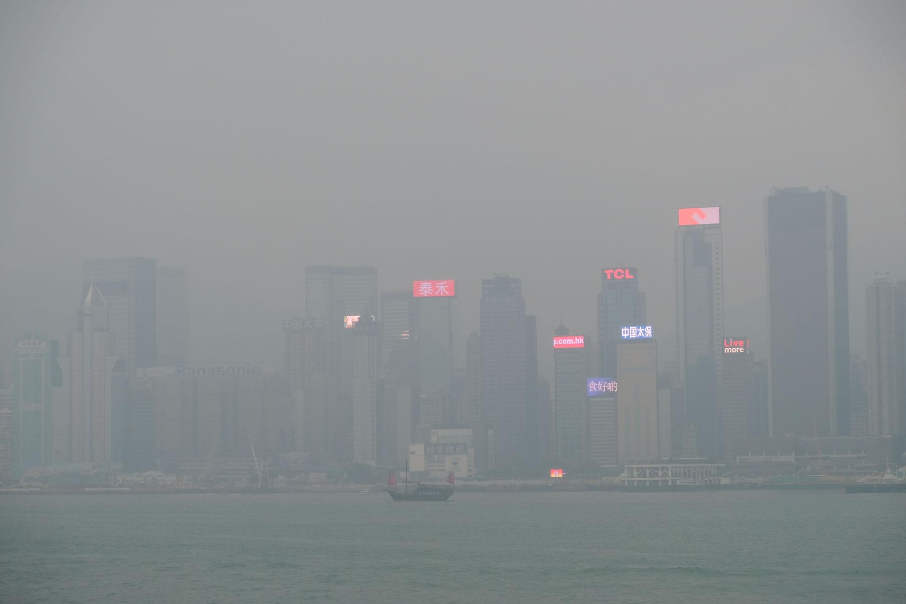 Ein Schiff mit roten Segeln fährt vor der Skyline Hongkongs vorbei, die im Nebel versinkt.