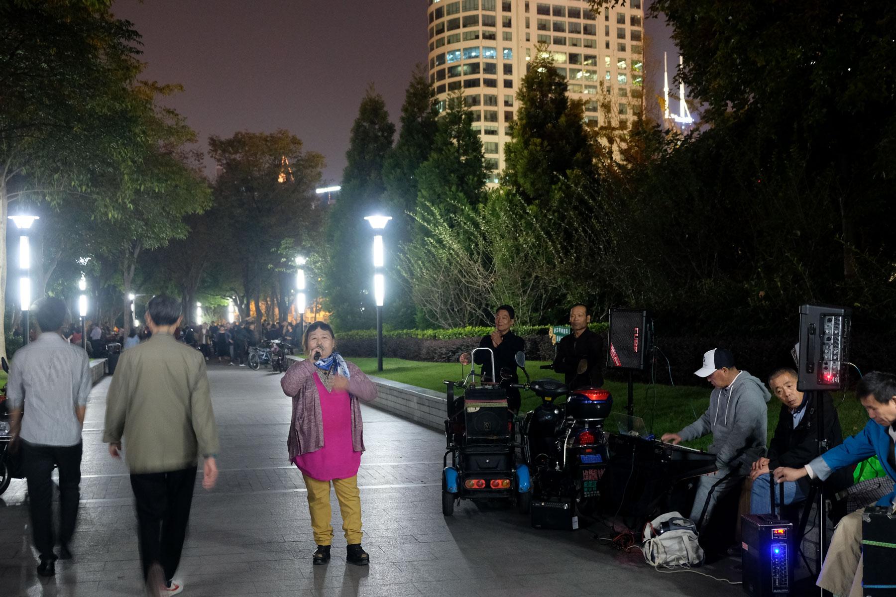 Eine Frau steht auf einem Platz in Shanghai und singt lauthals ins Mikrofon.