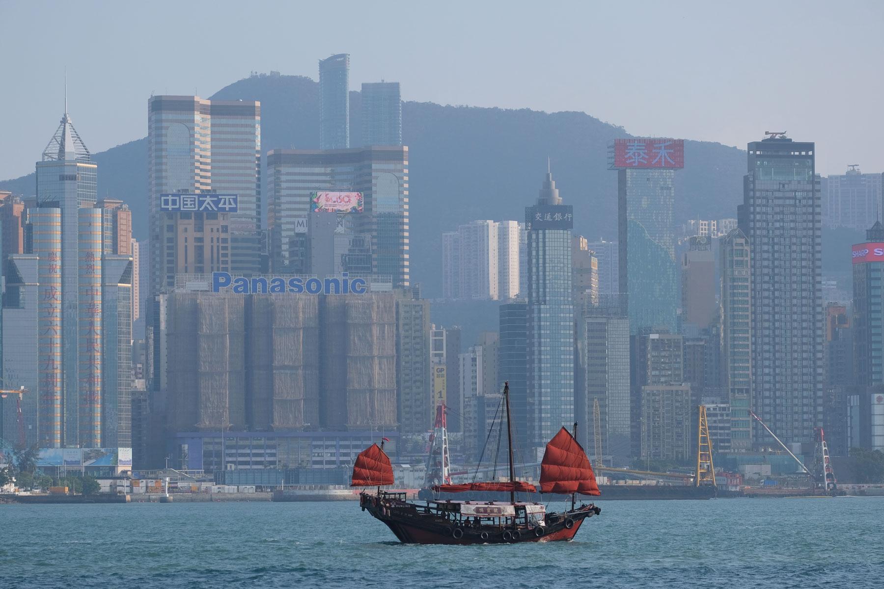 Ein Schiff mit roten Segeln fährt vor der Skyline Hongkongs vorbei