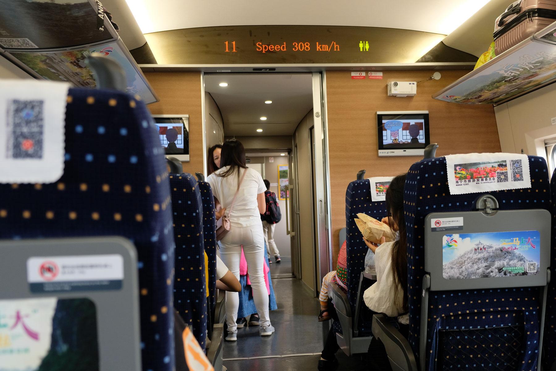Zwei Frauen stehen im Gang des Schnellzugs, der trotz 308 km/h erschütterungsfrei durch den Osten Chinas fliegt.