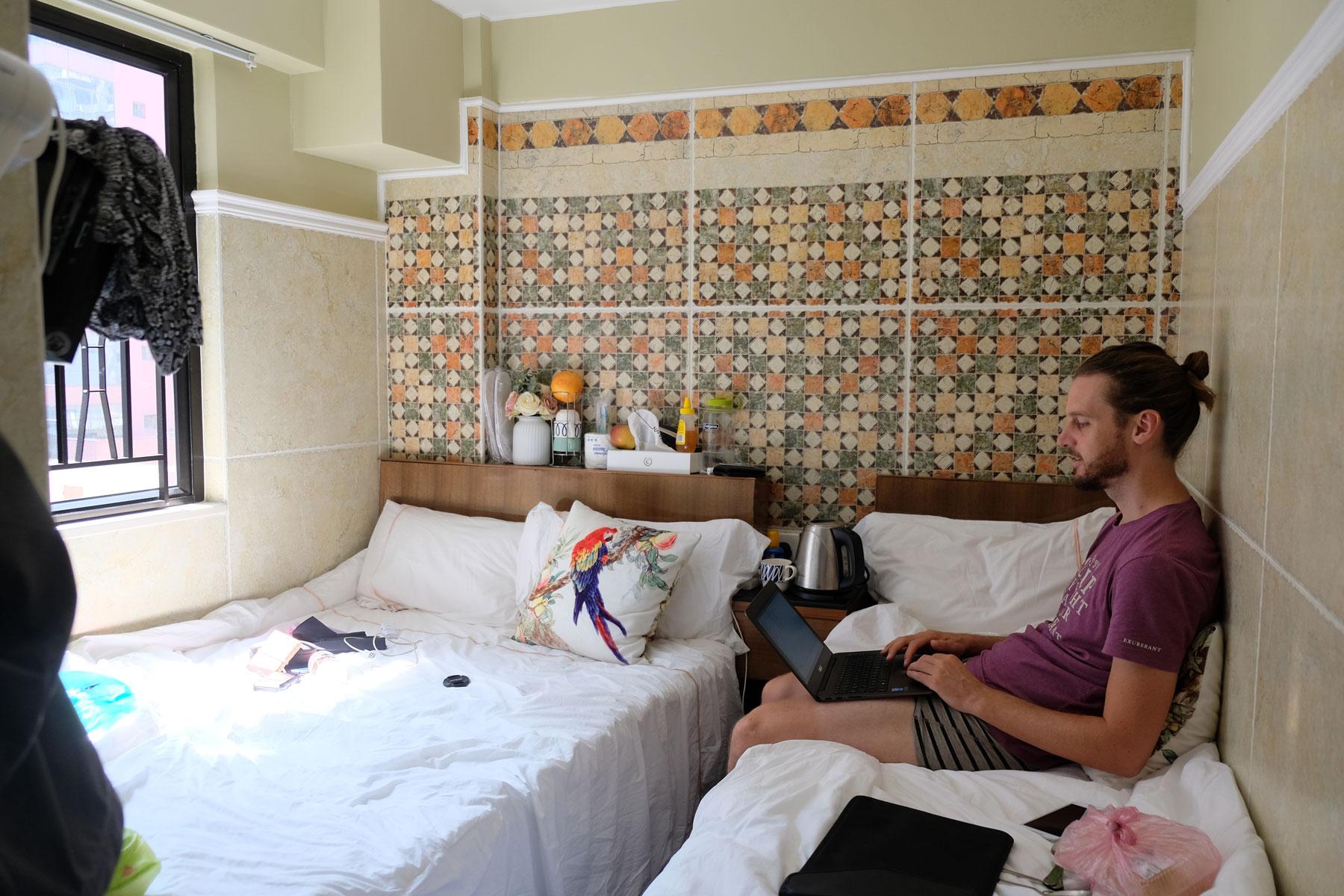 Sebastian sitzt auf dem Bett in unserem kleinen Hotelzimmer in Hongkong.