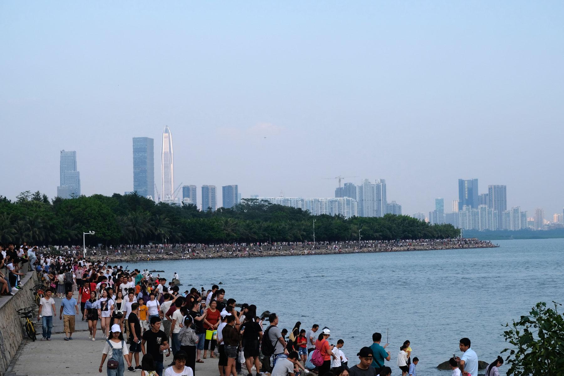 Am chinesischen Nationalfeiertag spazieren hunderte Menschen entlang der Bucht von Shenzhen.