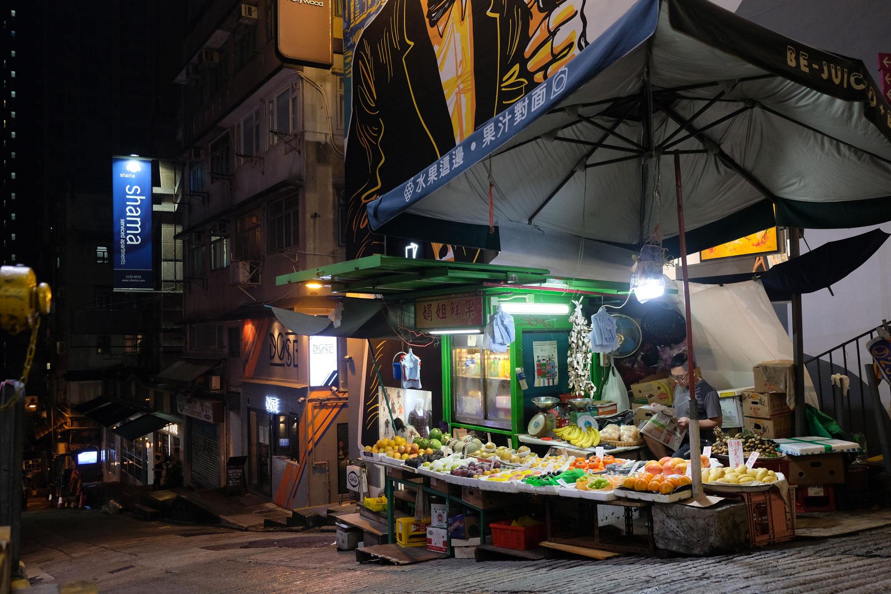 Ein beleuchteter Stand auf der Straße verkauft in der Dunkelheit Obst und Gemüse in Hongkong.