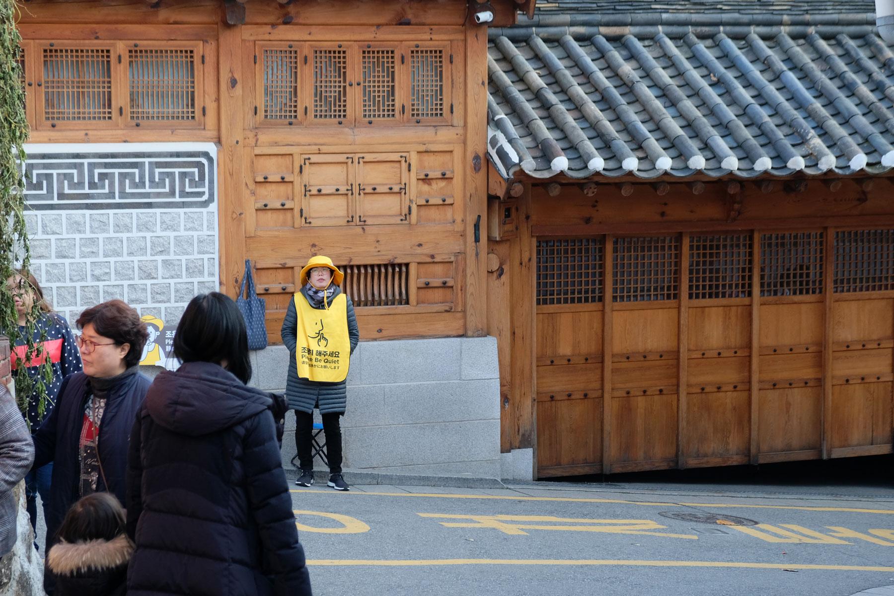 """Eine Aufpasserin trägt eine Weste mit der Aufschrift """"Please be quite!"""" im Bukchon Hanok Village in Seoul, Südkorea."""