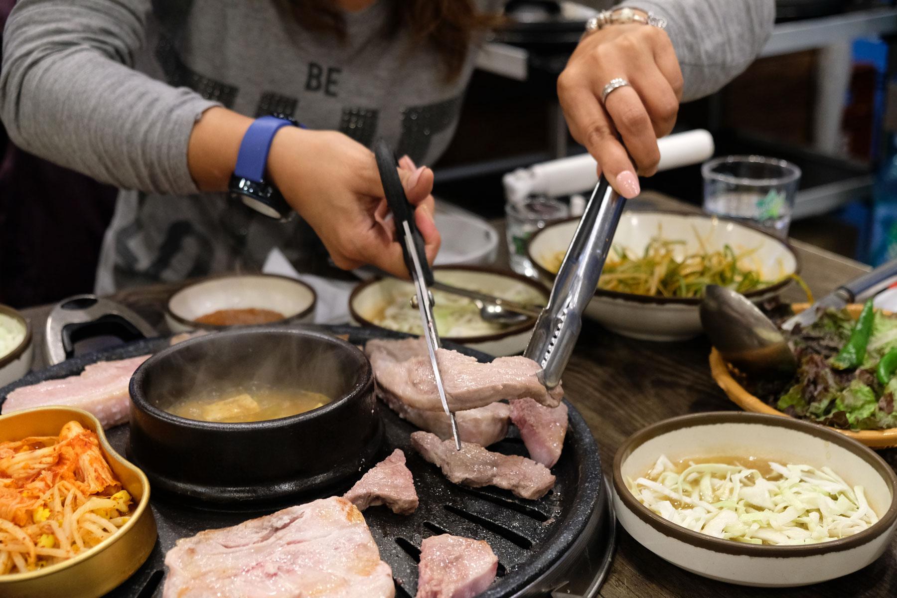 Ein Stück Fleisch wird mit der Schere kleingeschnitten.