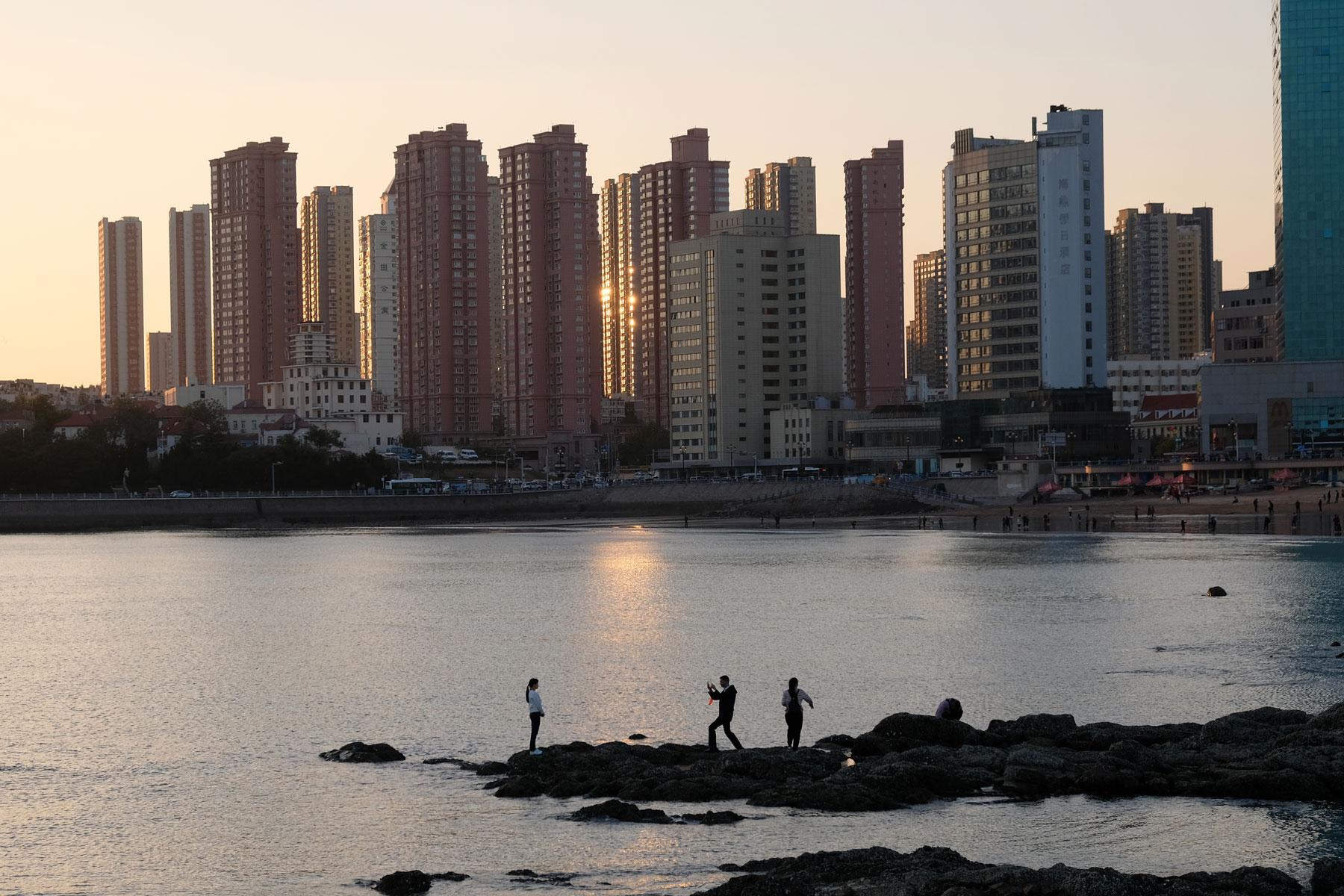 Ein Paar fofografiert sich vor der Skyline Qingdaos in China.