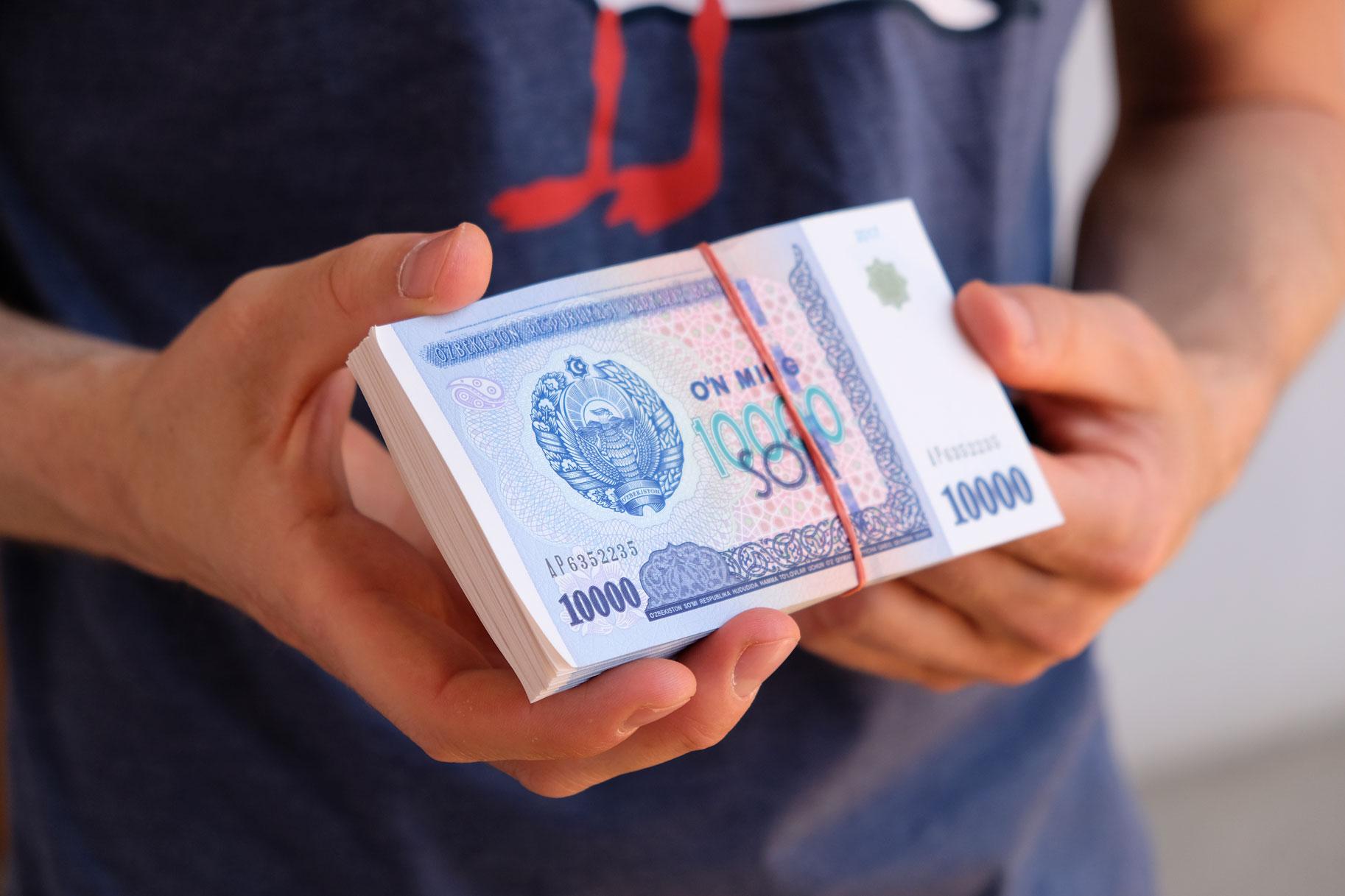 Zwei Hände halten einen Bündel Geldscheine aus Usbekistan.