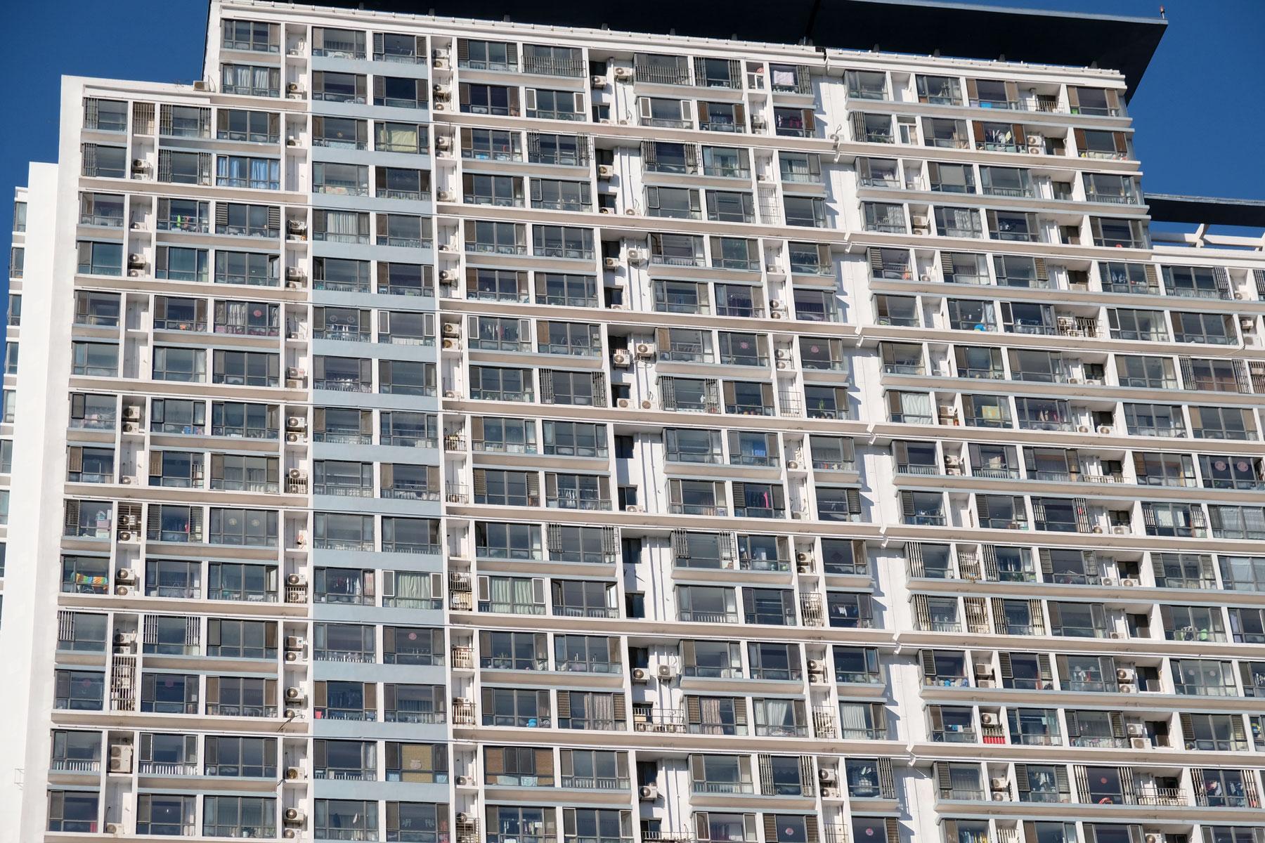Die Fensterfassade eines Hochhauses in Qingdao in China.
