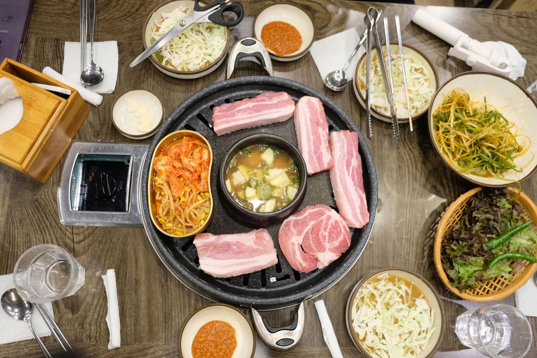 Ein Tisch ist für das koreanische Barbeque vorbereitet, bei dem dicke Scheiben Fleisch gegrillt werden.