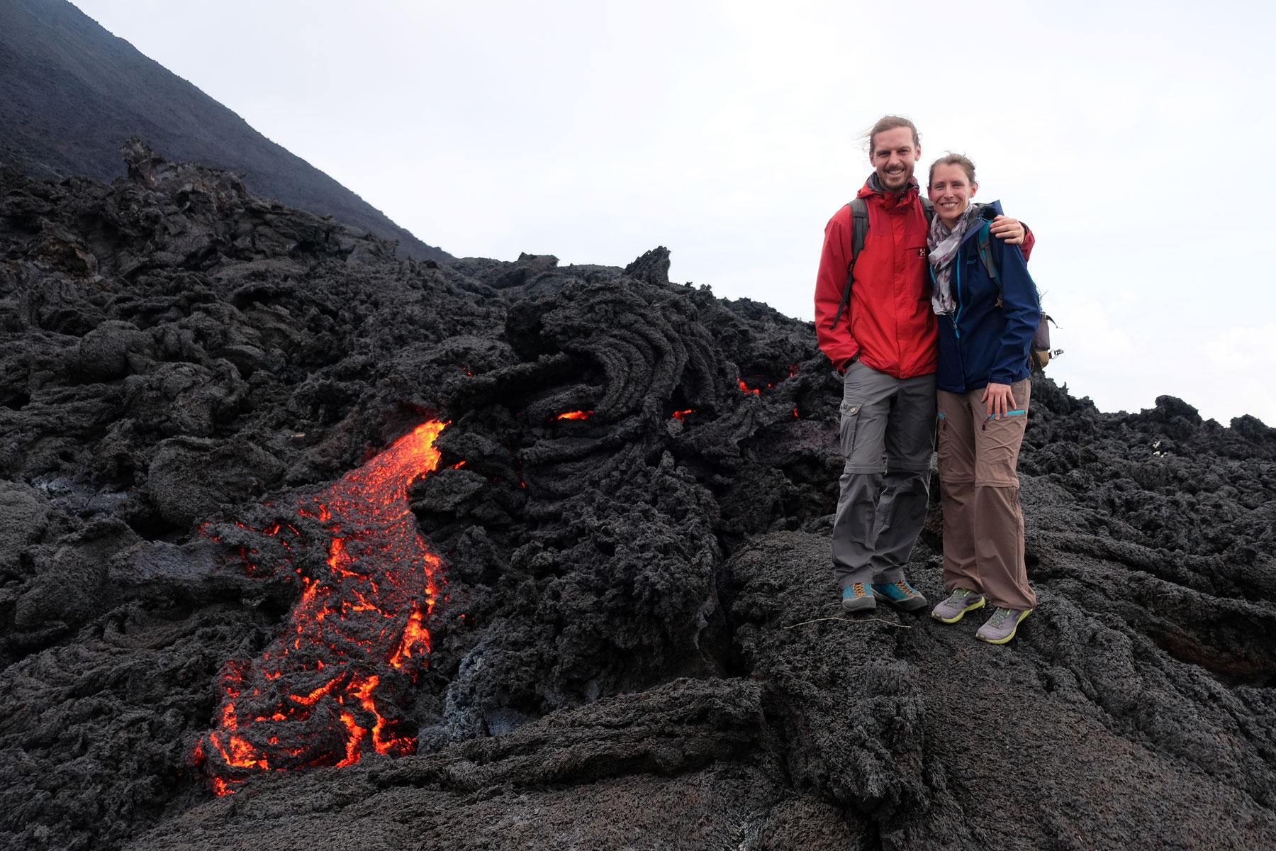 Leo und Sebastian stehen einen Meter entfernt von rot glühendem, heißen Magma am Vulkan Pacaya in Guatemala.