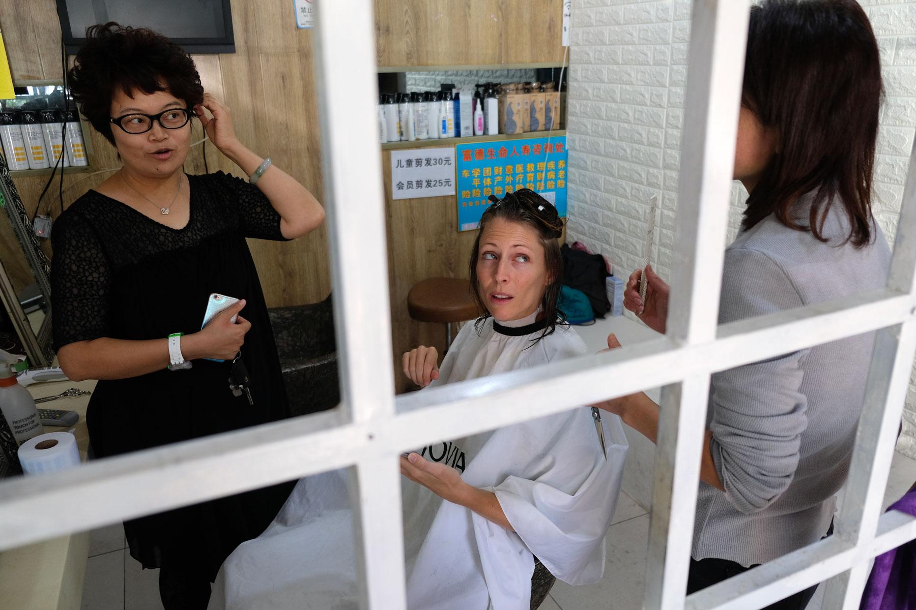 Leo und Sunny erklären der Frisörin in Qingdao in China, wie Leos Haarschnitt aussehen soll.