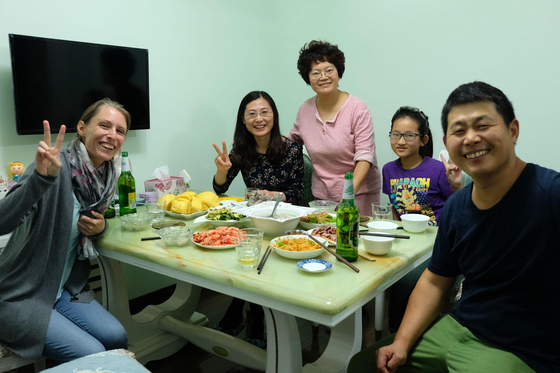 Leo sitzt mit den Gastgebern zusammen am Abendessenstisch in Qingdao, China.