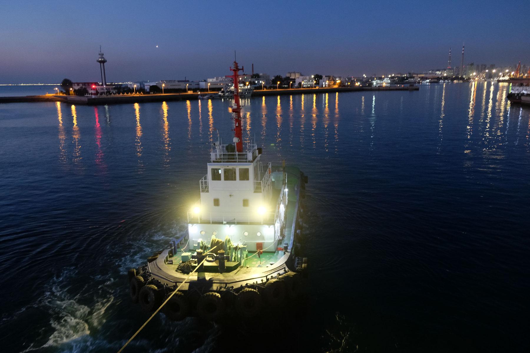 Ein Schleppschiff zieht in der Dunkelheit unsere Fähre aus dem Hafen Qingdao in China.