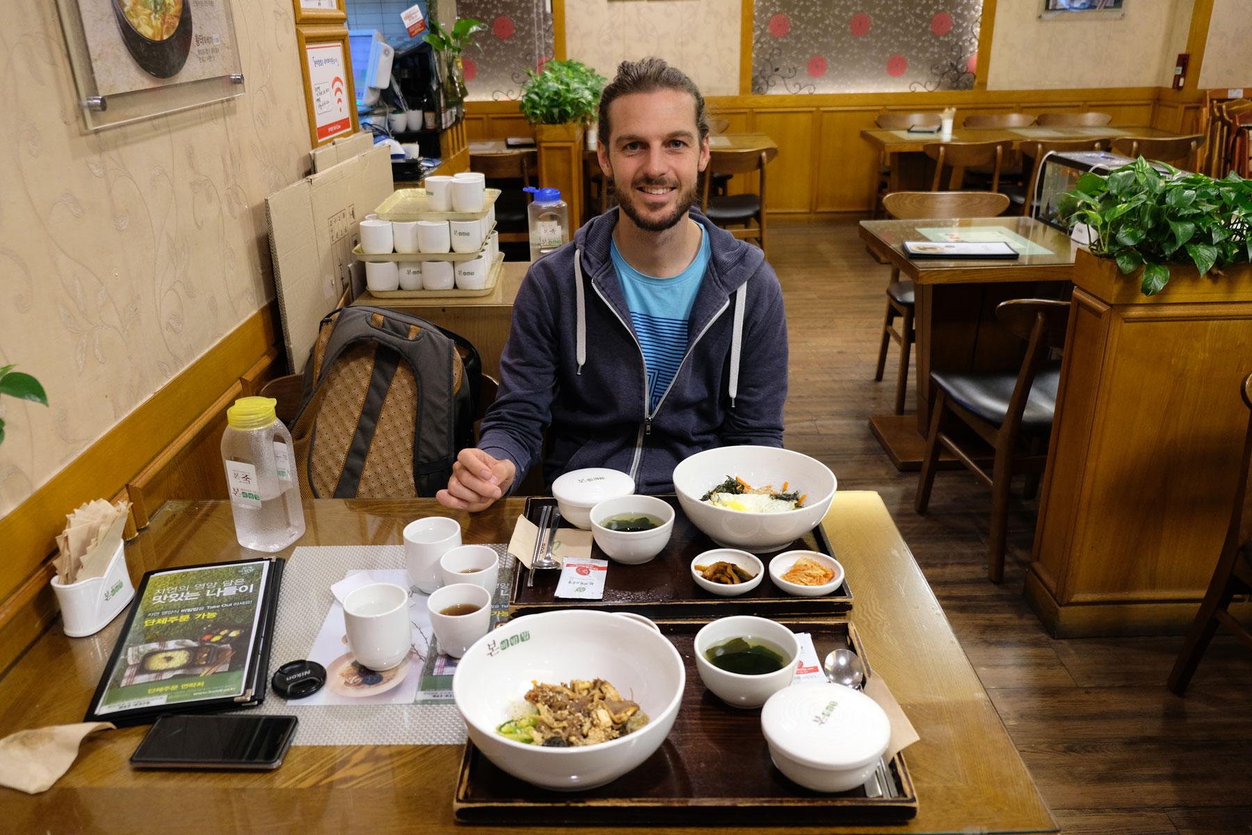 Sebastian sitzt in Südkorea im Restaurant und isst Bibimbap.