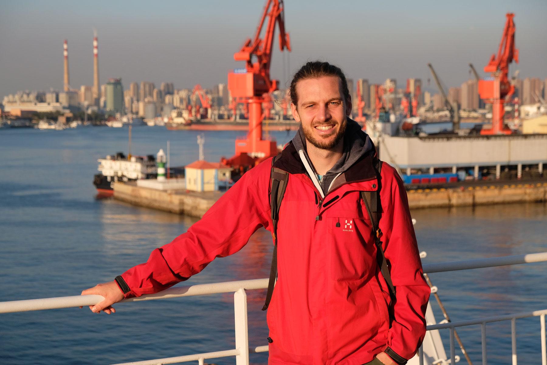 Sebastian steht an der Rehling unserer Fähre nach Südkorea, hinter ihm der Hafen von Qingdao in China.