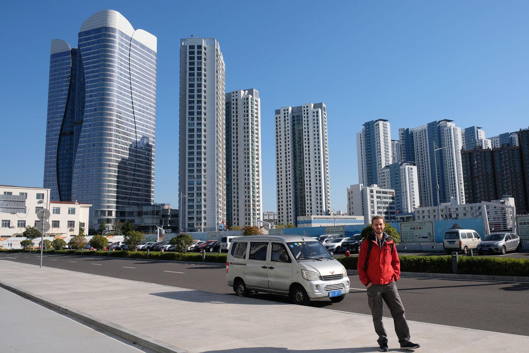 Sebastian steht vor einigen Hochhäusern Qingdaos in China.