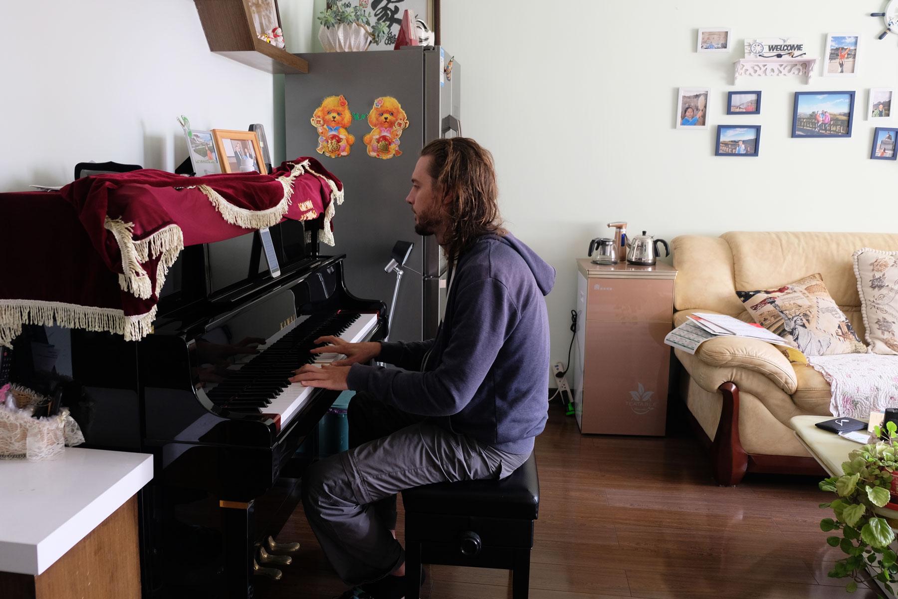 Sebastian spielt Klavier im Wohnzimmer von Sunny und Terry.