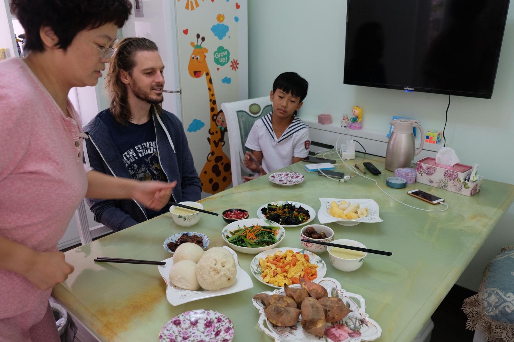 Sebastian und Yang Yang sitzen am von Sunny vorbereiteten Frühstückstisch.