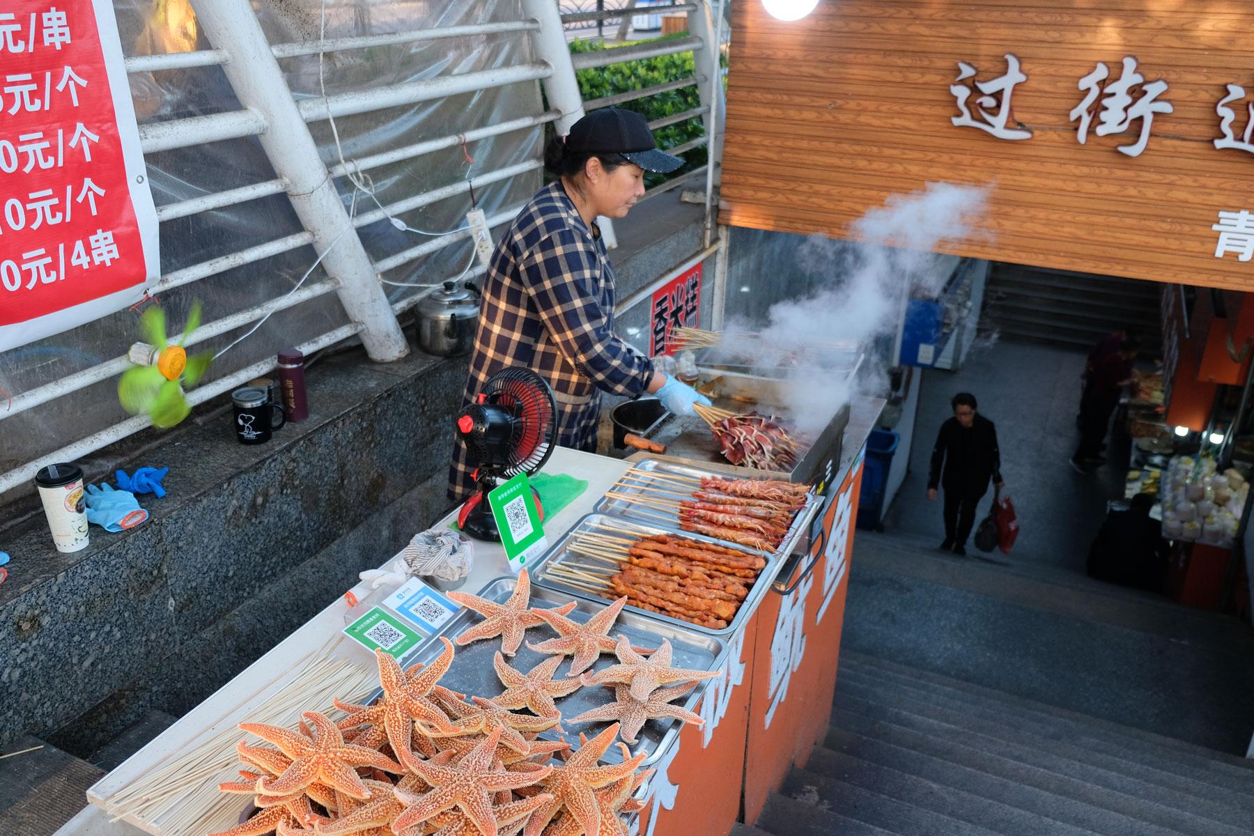 Eine Frau verkauft Seesterne und Fleischspieße in Qingdao in China.