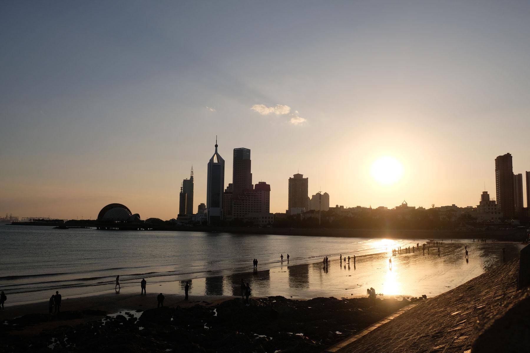 Die Sonne geht hinter den Hochhäusern von Qingdao unter.