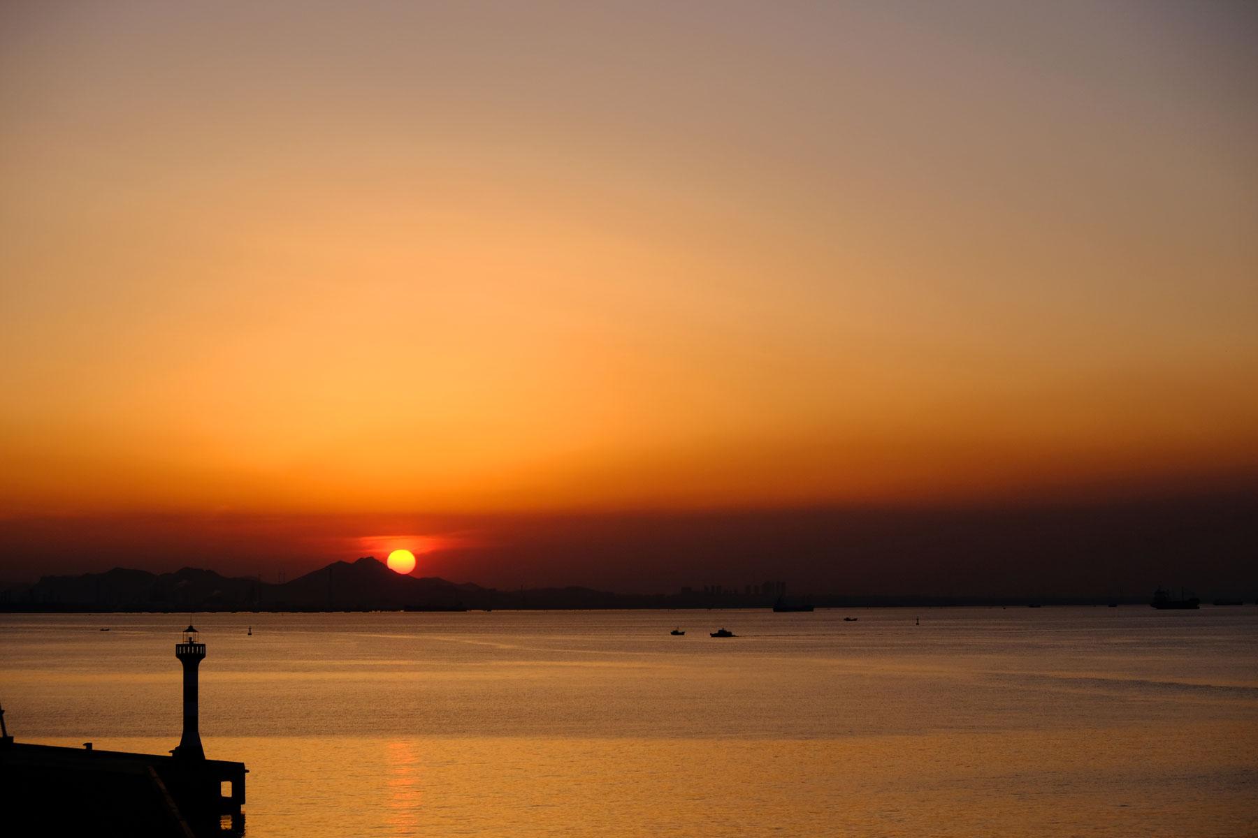 Über dem Hafen von Qingdao in China geht die Sonne unter.
