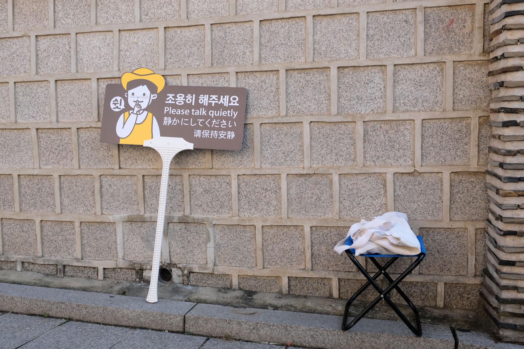"""Ein Schild mit der Aufschrift """"bitte leise reden"""" lehnt an einer Wand im Bukchon Hanok Village in Südkorea."""