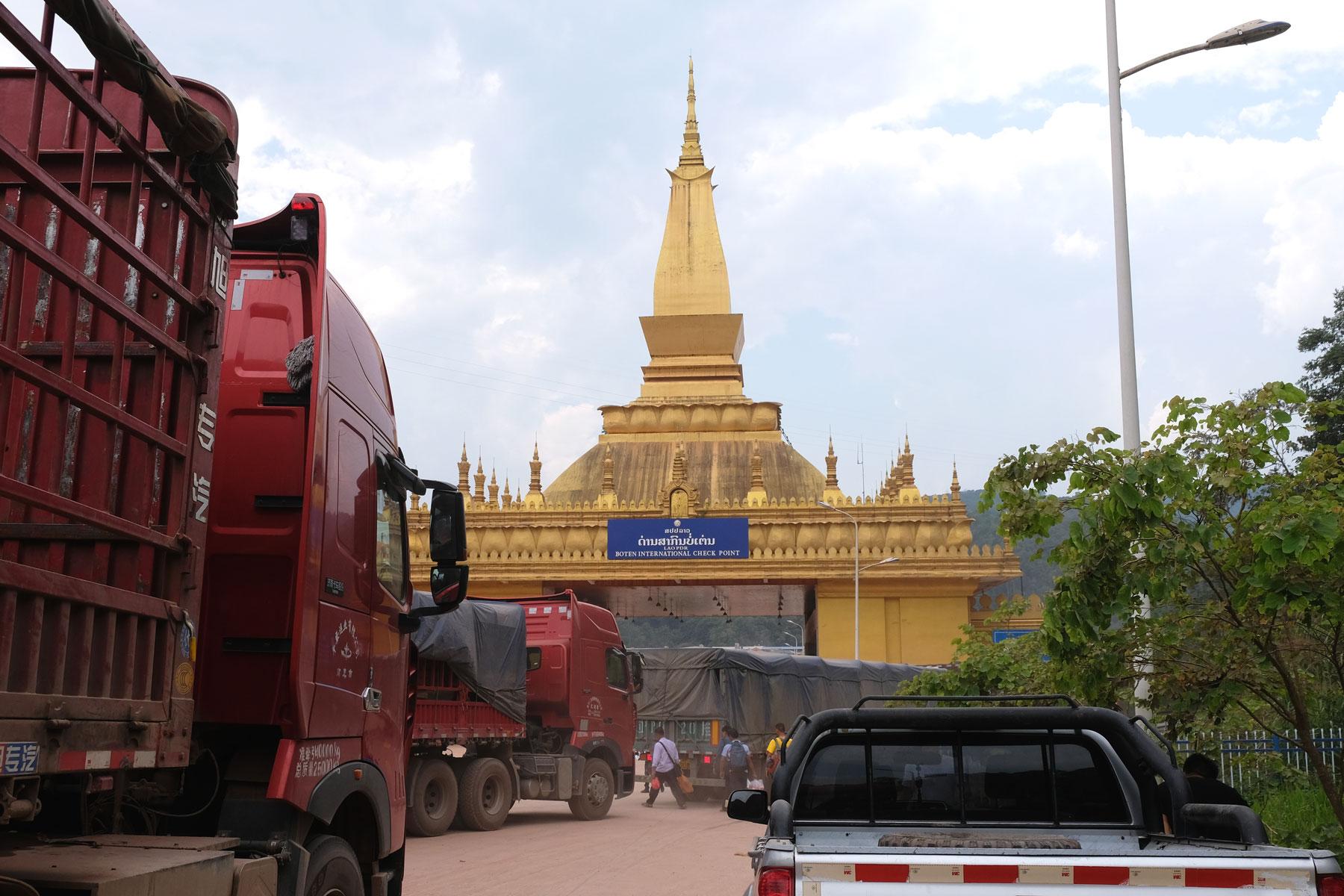 Eine Stupa und Lastwagen am Grenzübergang Mohan zwischen China und Laos.
