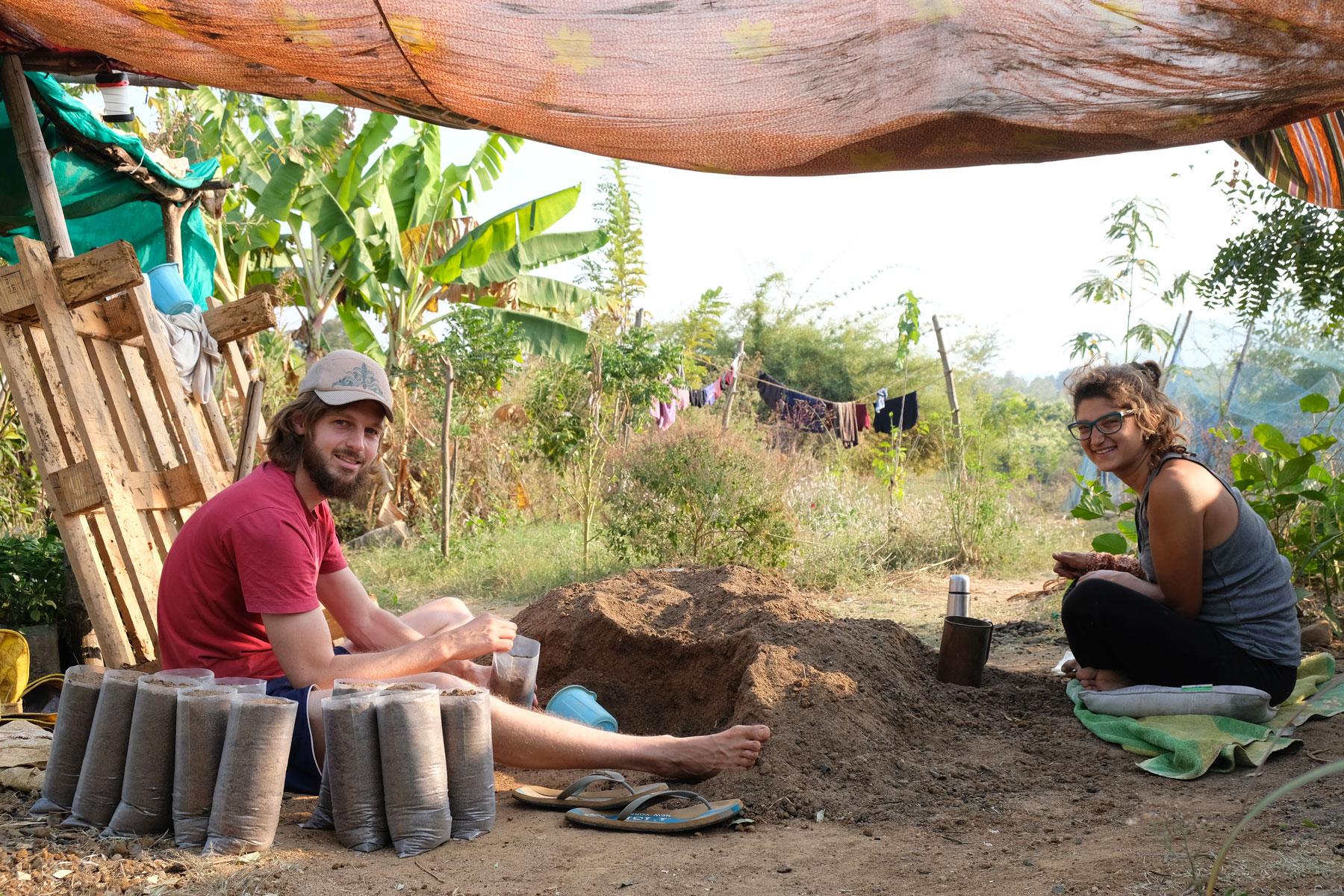 Sebastian füllt mit einer Freiwilligen beim Workaway Erde in Säckchen.