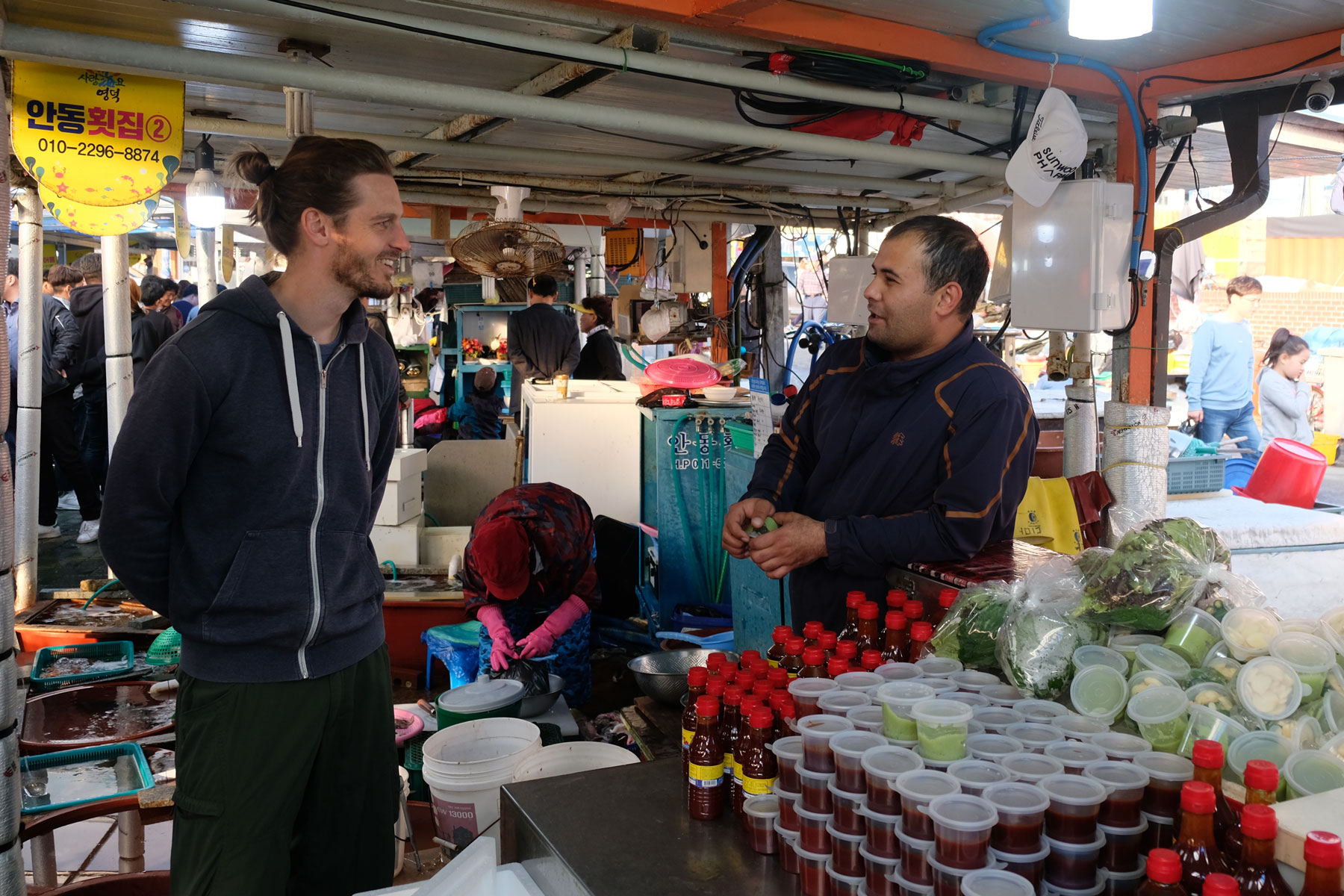 Sebastian unterhält sich mit einem Verkäufer am Fischmarkt in Gonggu in Südkorea.
