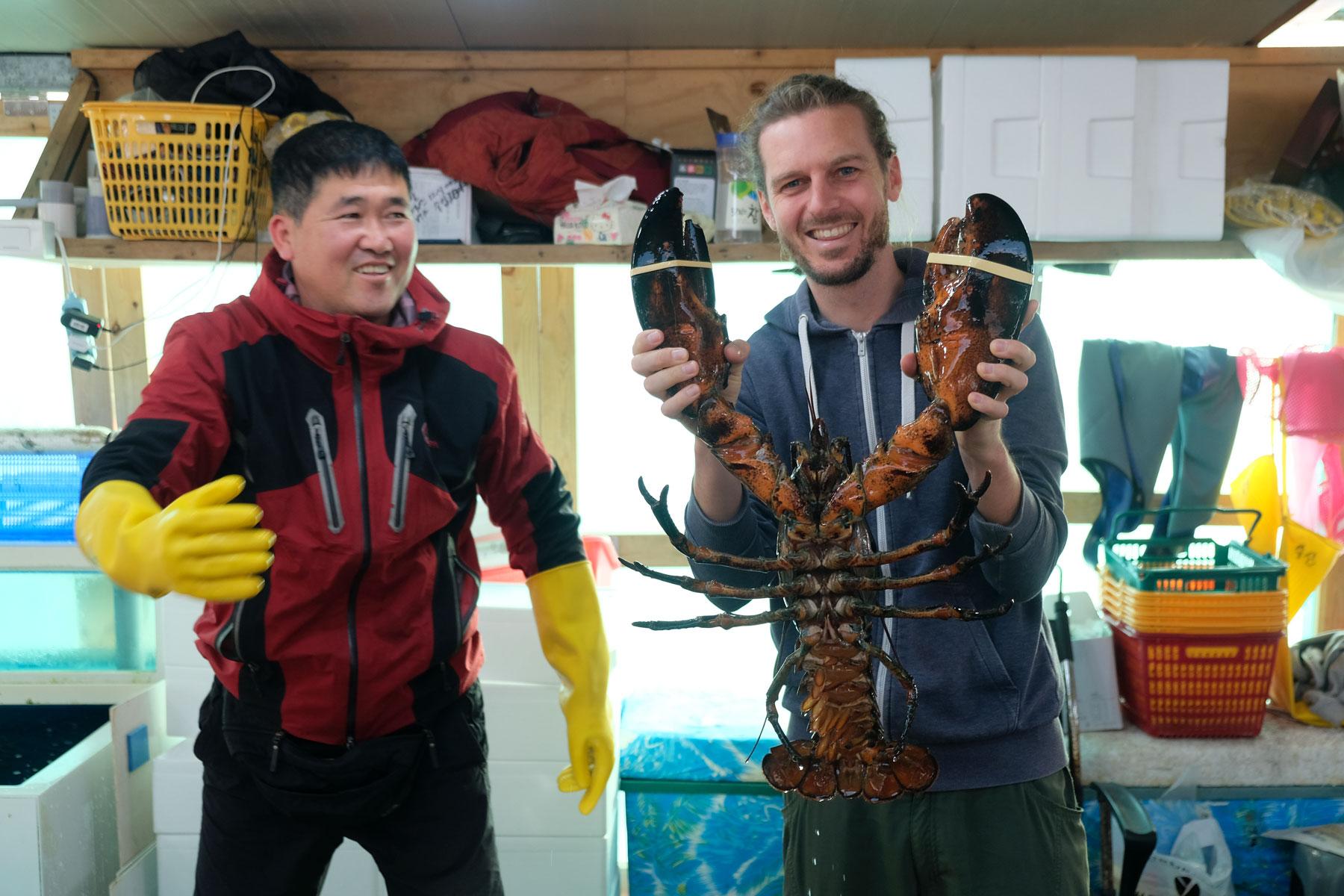 Sebastian hält einen Riesenhummer auf dem Fischmarkt in Südkorea.