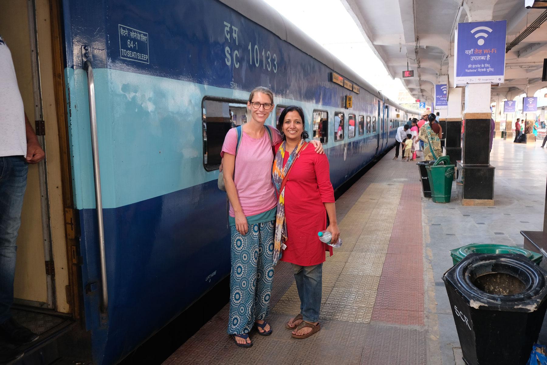 Leo steht mit einer Frau neben einem Zug im Bahnhof von Hyderabad.
