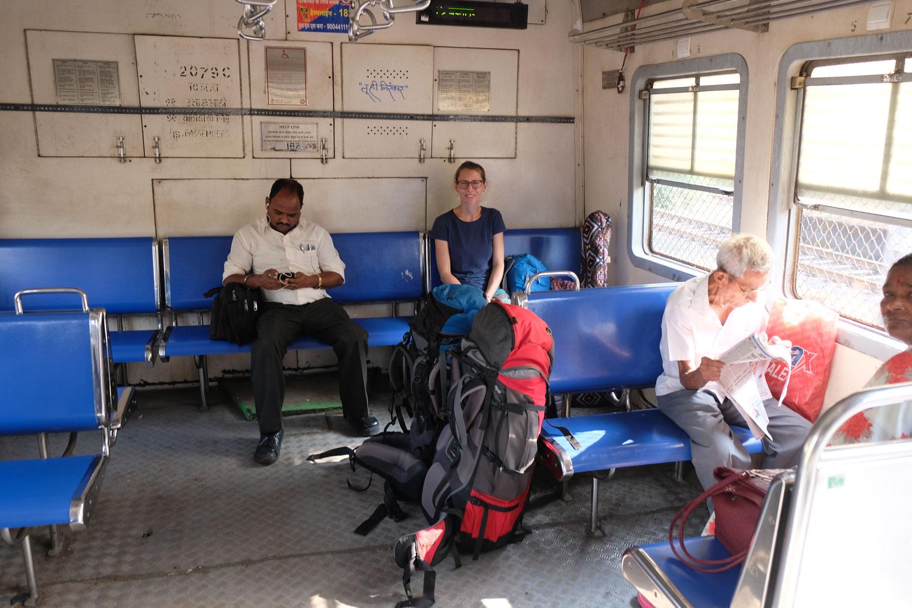 Leo sitzt mit anderen Fahrgästen in einem Regionalzug in Mumbai.