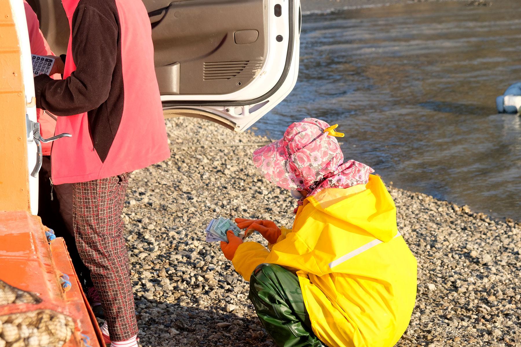 Eine Muschelsammlerin zählt ihren Verdienst in Socheon, Südkorea.