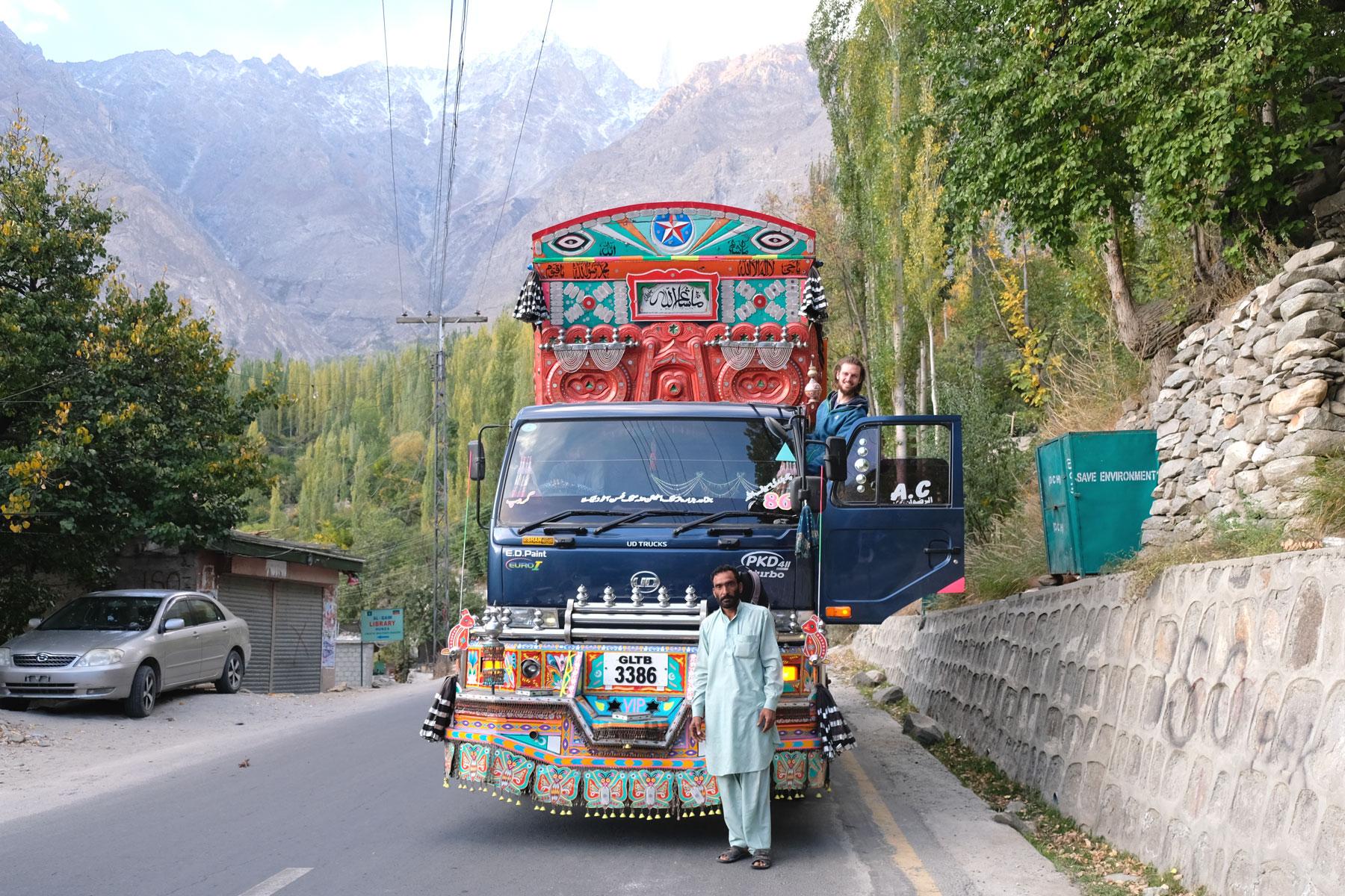 Ein Mann steht vor einem reich verzierten Lastwagen in Pakistan.