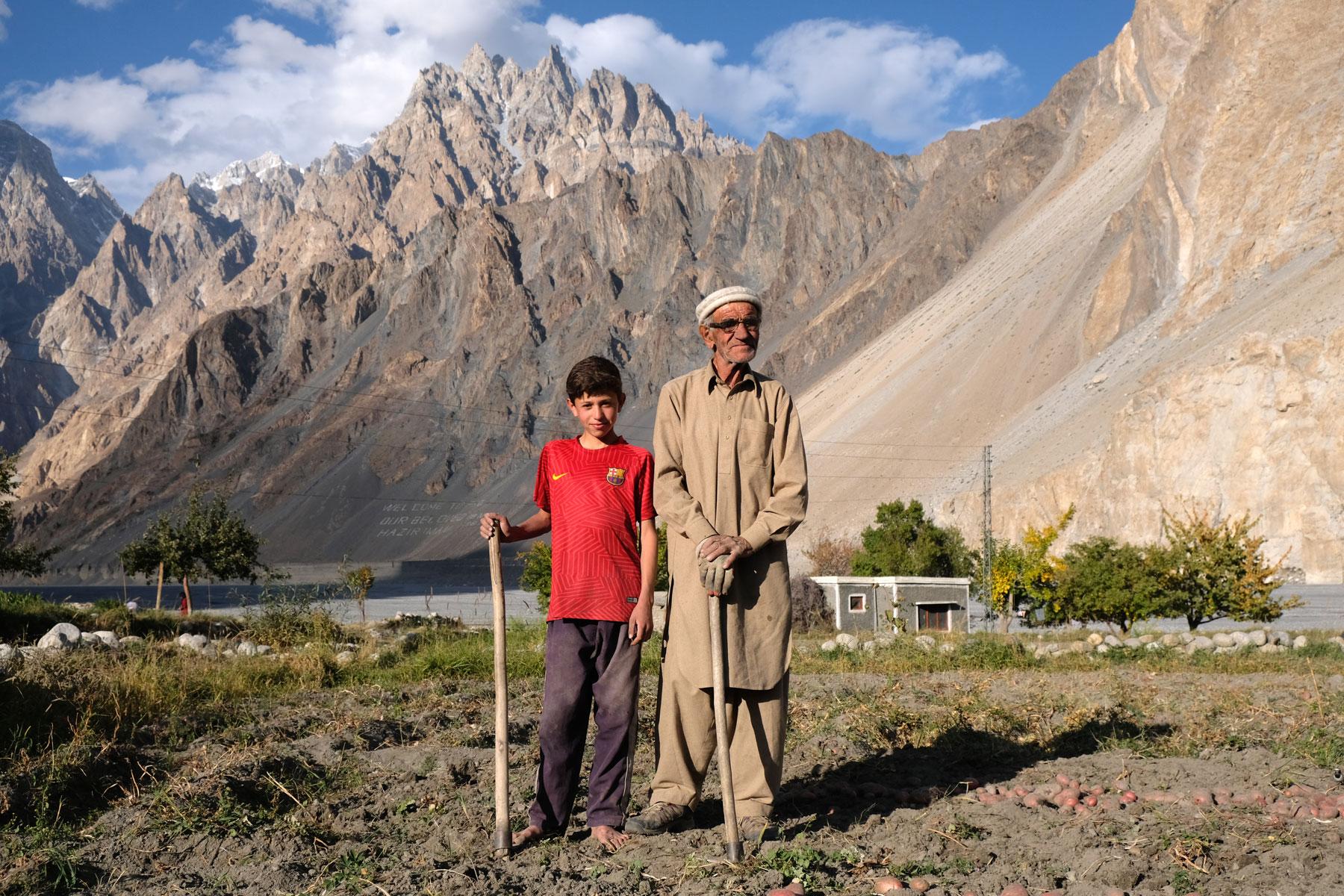 Ein alter Mann und ein Junge stehen auf einem Feld vor einer Bergkulisse im Hunza Tal.