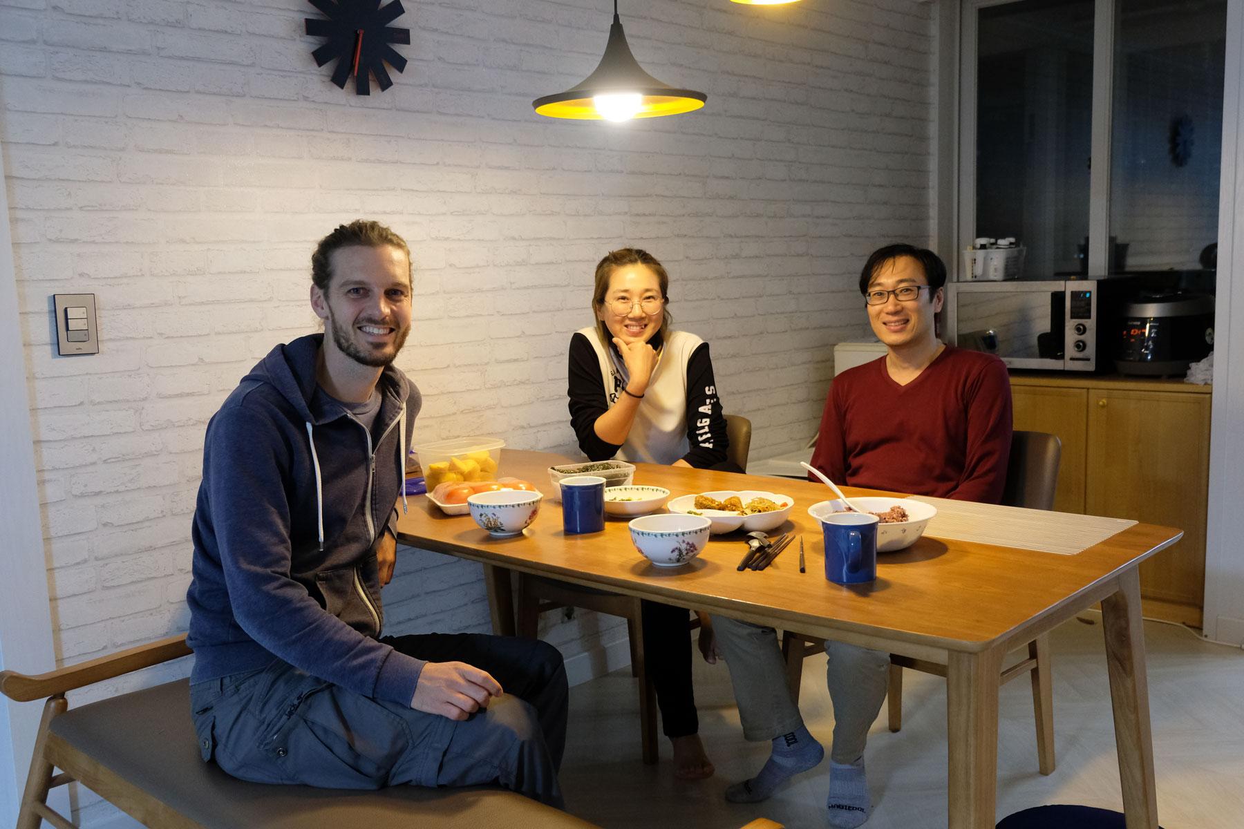 Sebastian sitzt mit unseren Couchsurfing-Gastgebern in Südkorea am Esstisch.