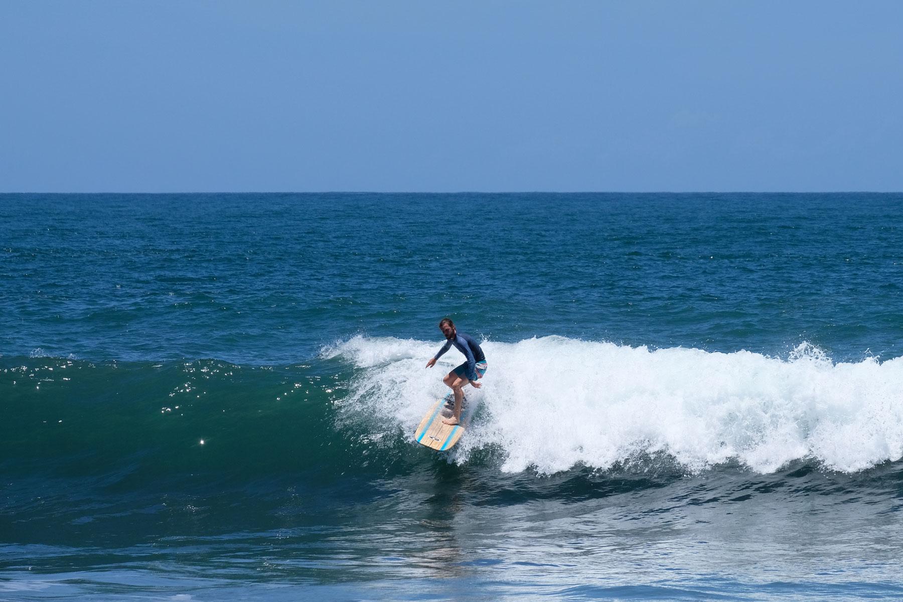 Sebastian surft auf einer Welle in El Salvador.