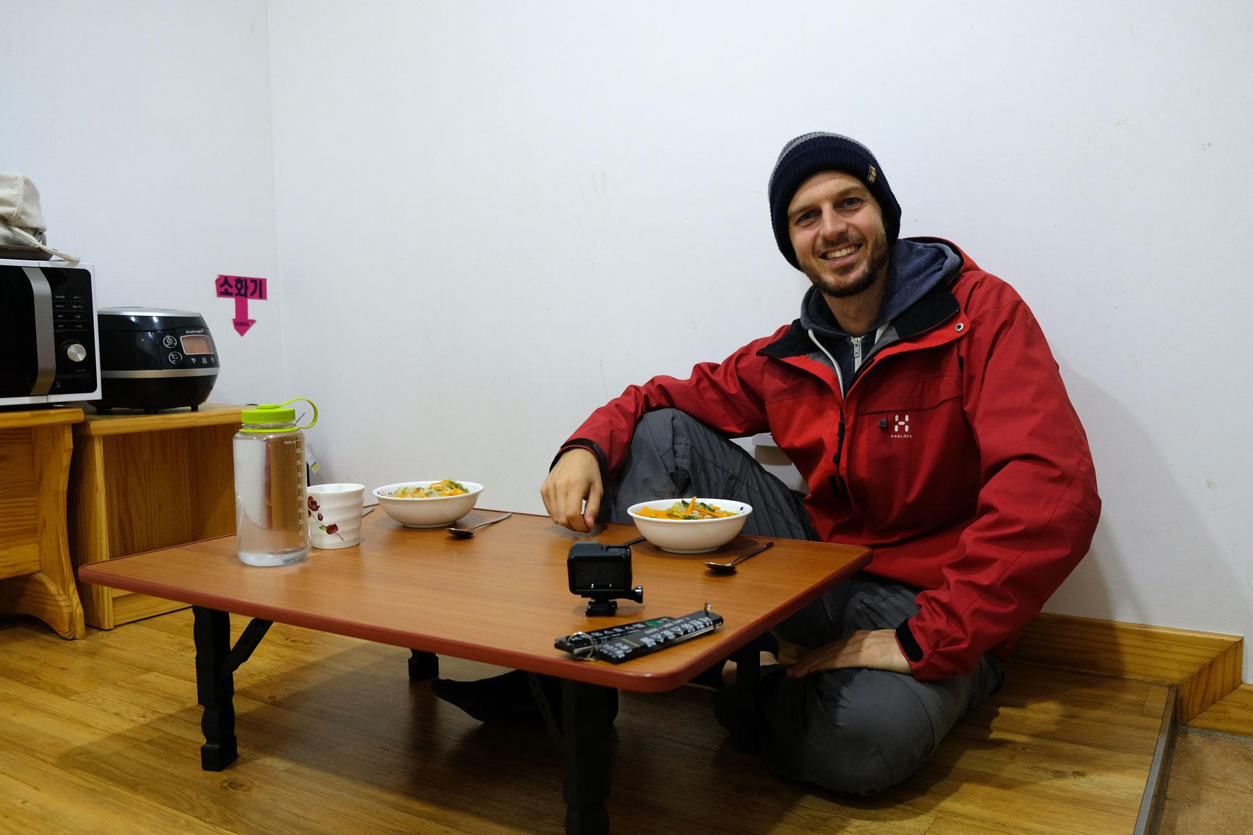Sebastian sitzt an einem niedrigen Tisch in Südkorea.