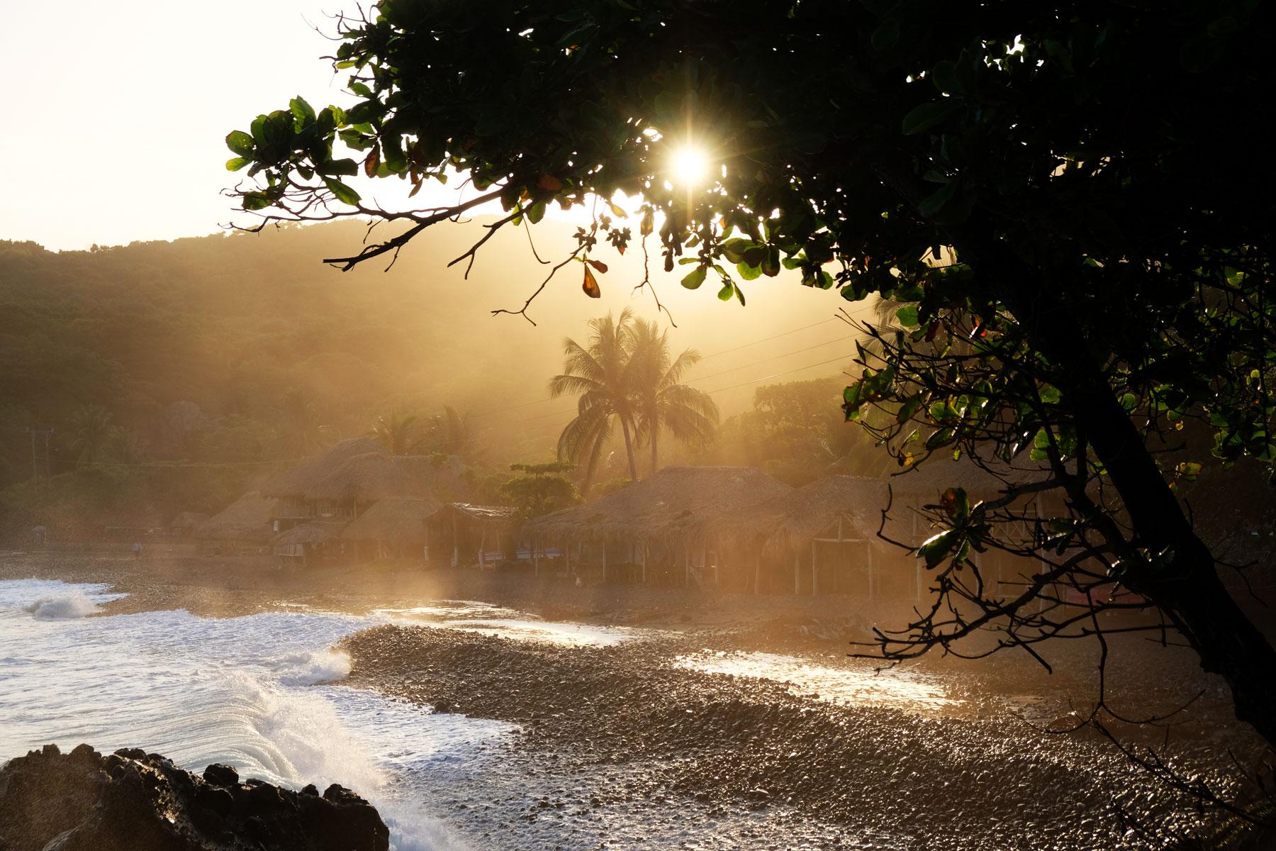 Der Strand El Palmarcito in El Salvador leuchtet golden im Licht der untergehenden Sonne.