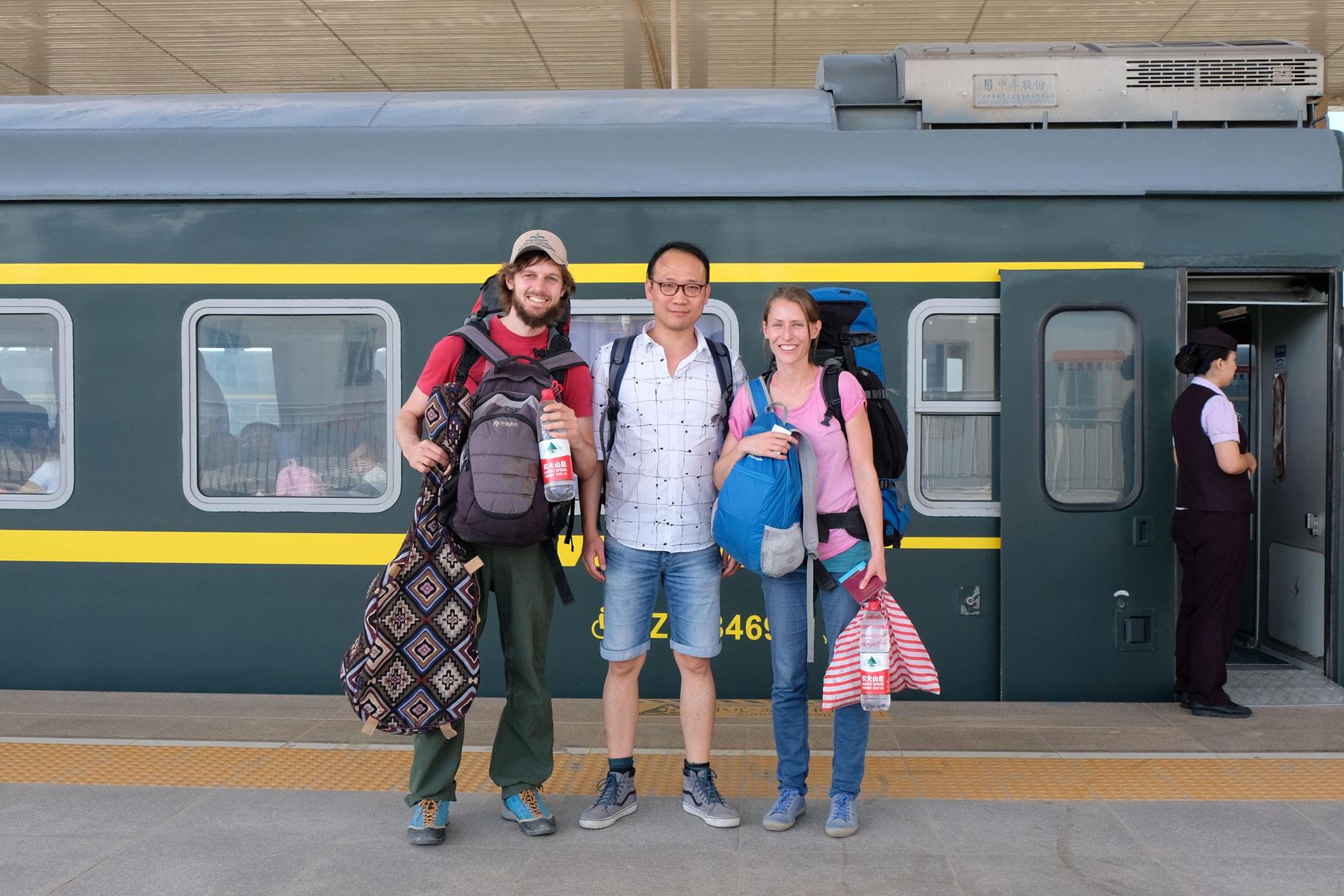 Sebastian und Leo mit einem Chinesen vor einem Zug am Bahnsteig.